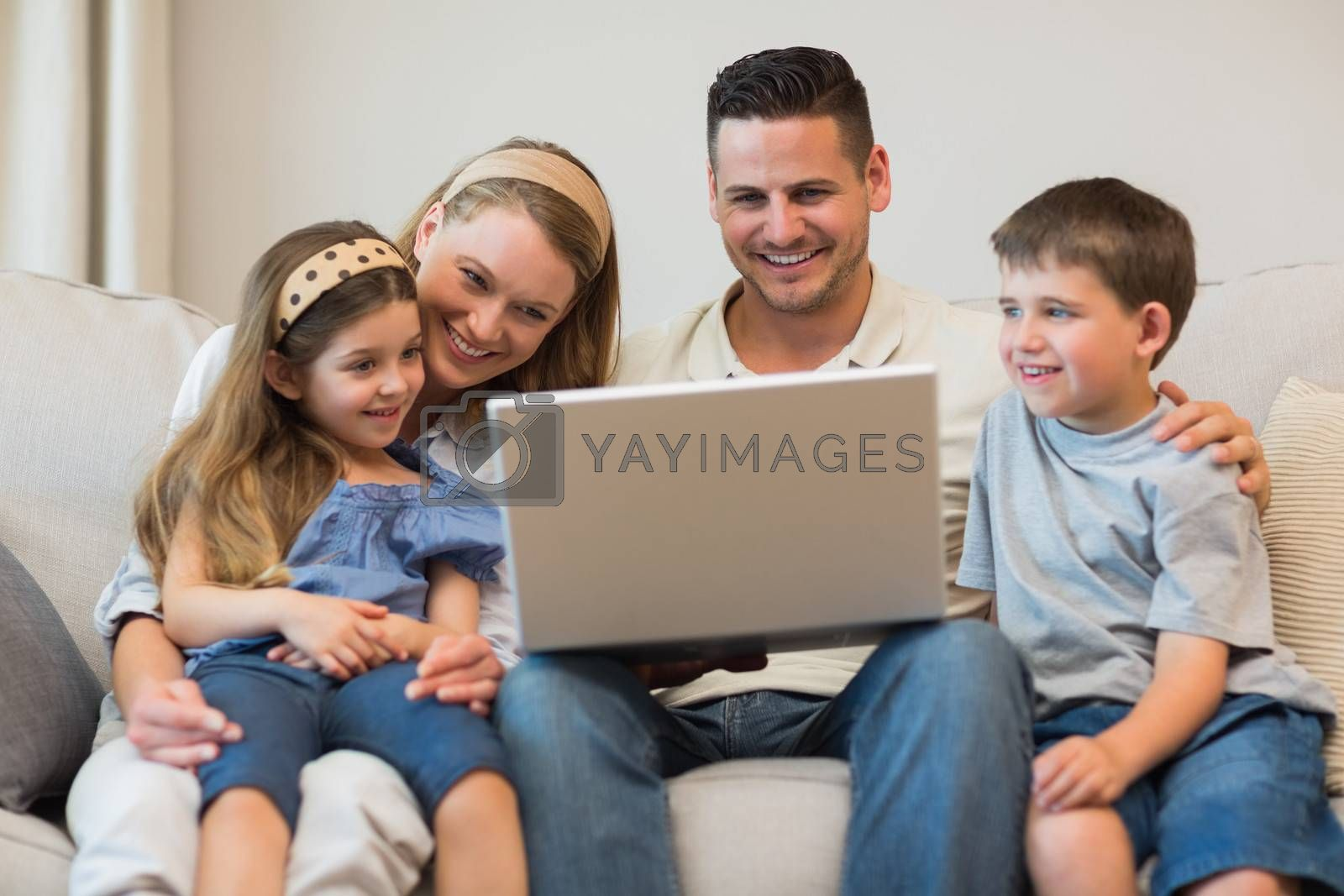 Happy family using laptop together on sofa in house
