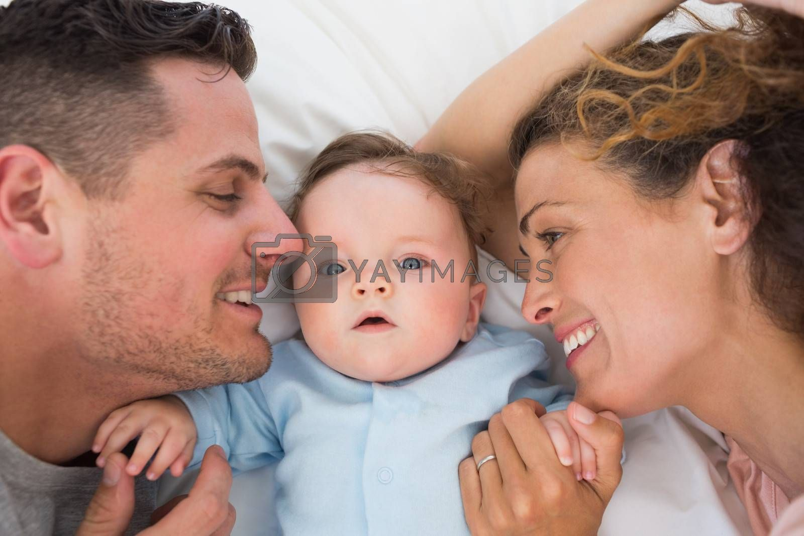 Portrait of cute baby boy with parents in bed