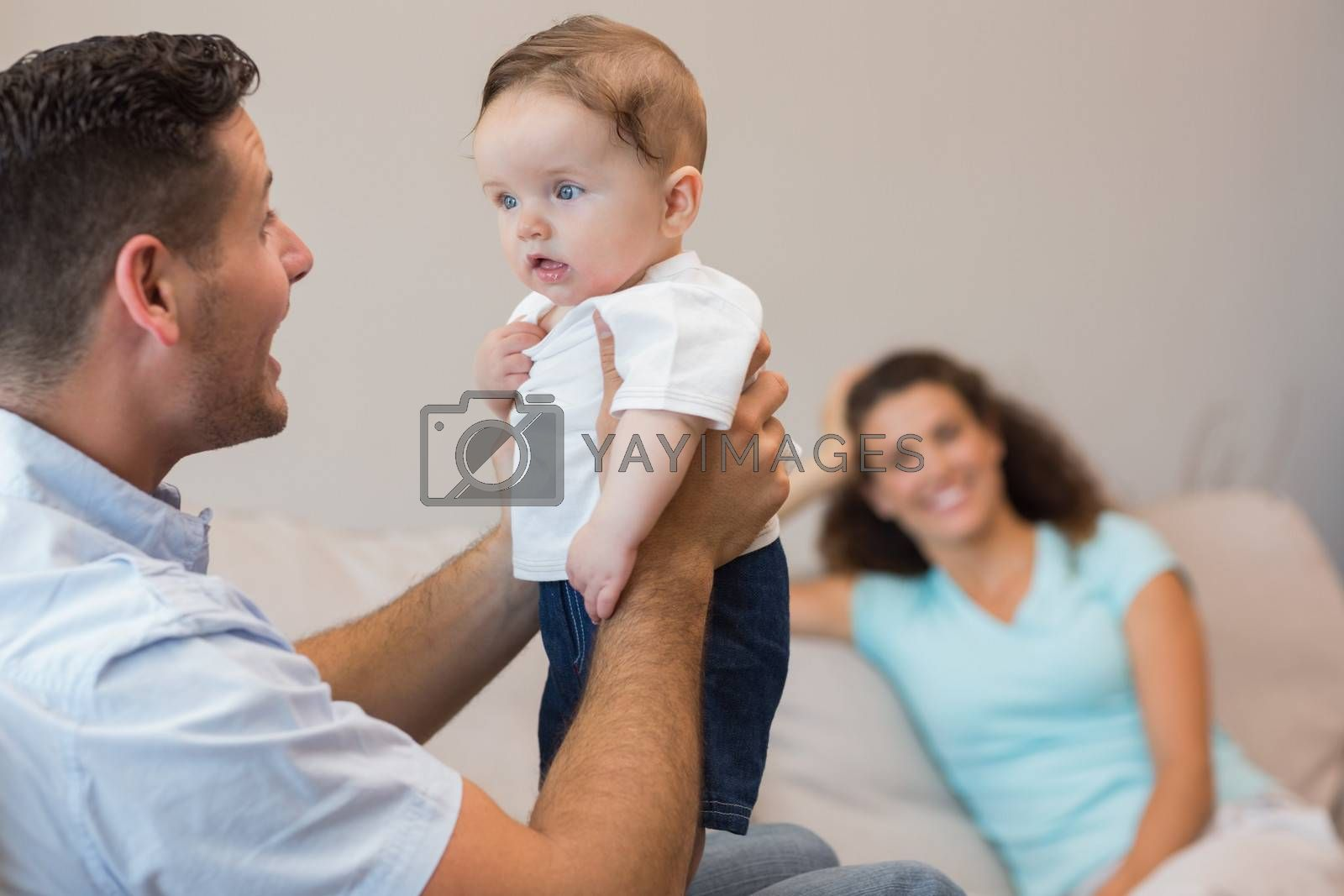 Happy man playing with cute baby while woman sitting in background at home