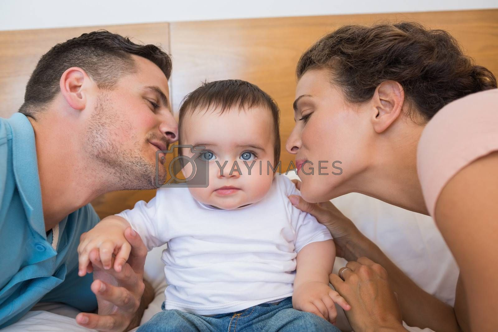 Loving parents kissing baby boy on cheek in bed