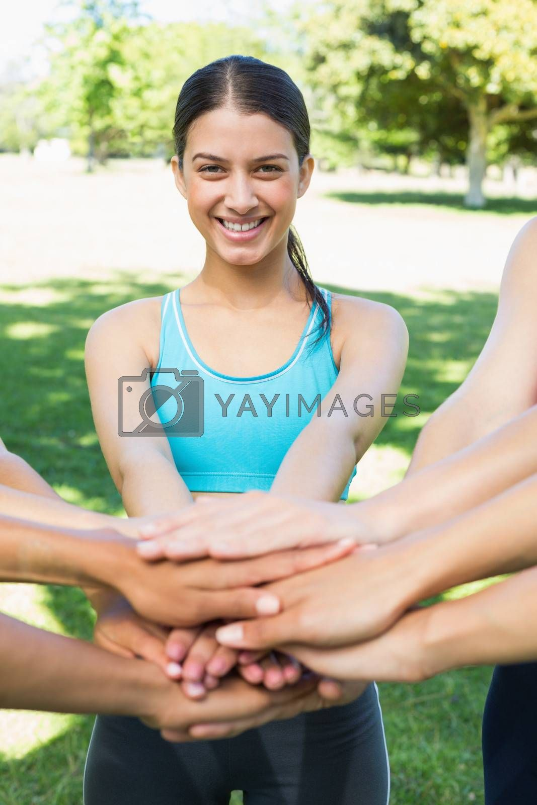 Portrait of happy fit woman stacking hands with friends in park