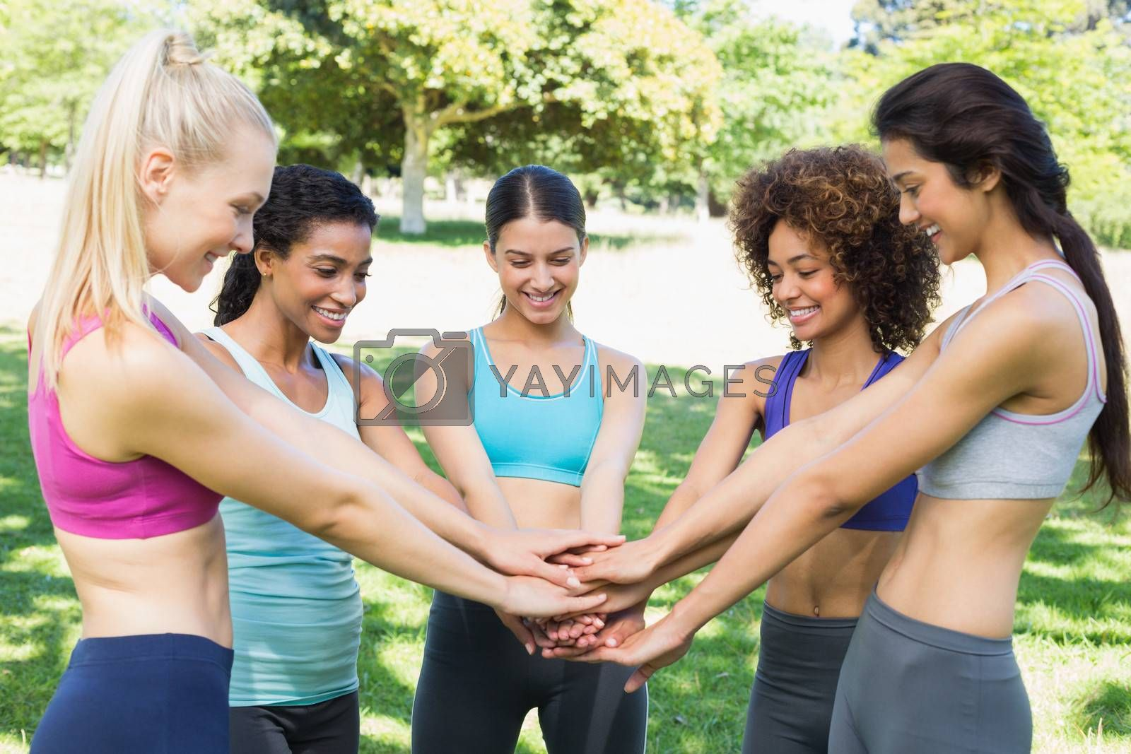 Fit young women stacking hands together in the park