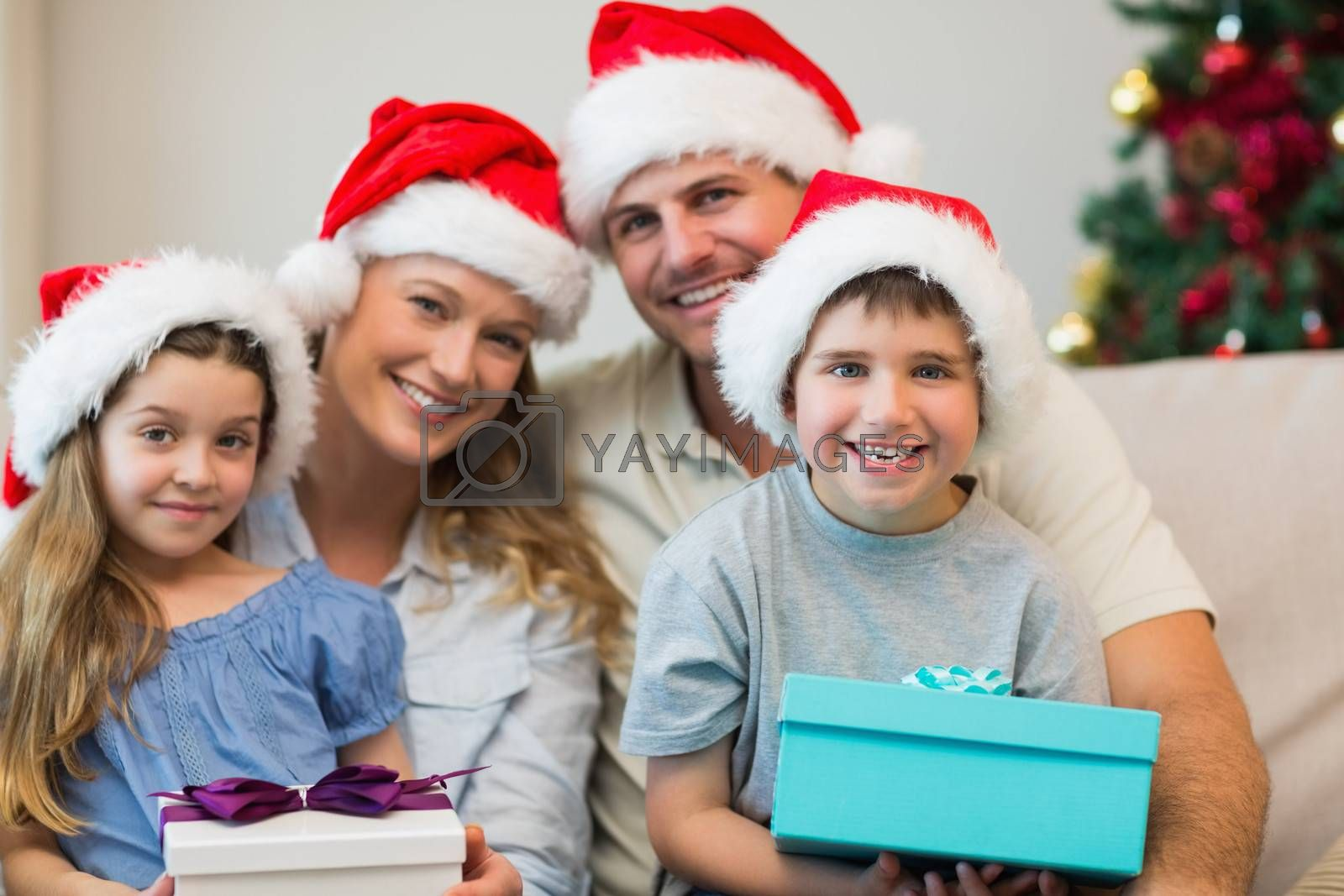 Portrait of happy family wearing Christmas hat while holding presents on sofa at home