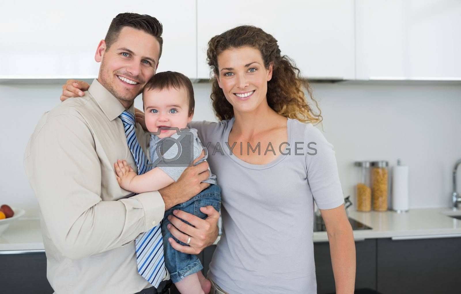 Portrait of smiling parents with cute baby boy in kitchen