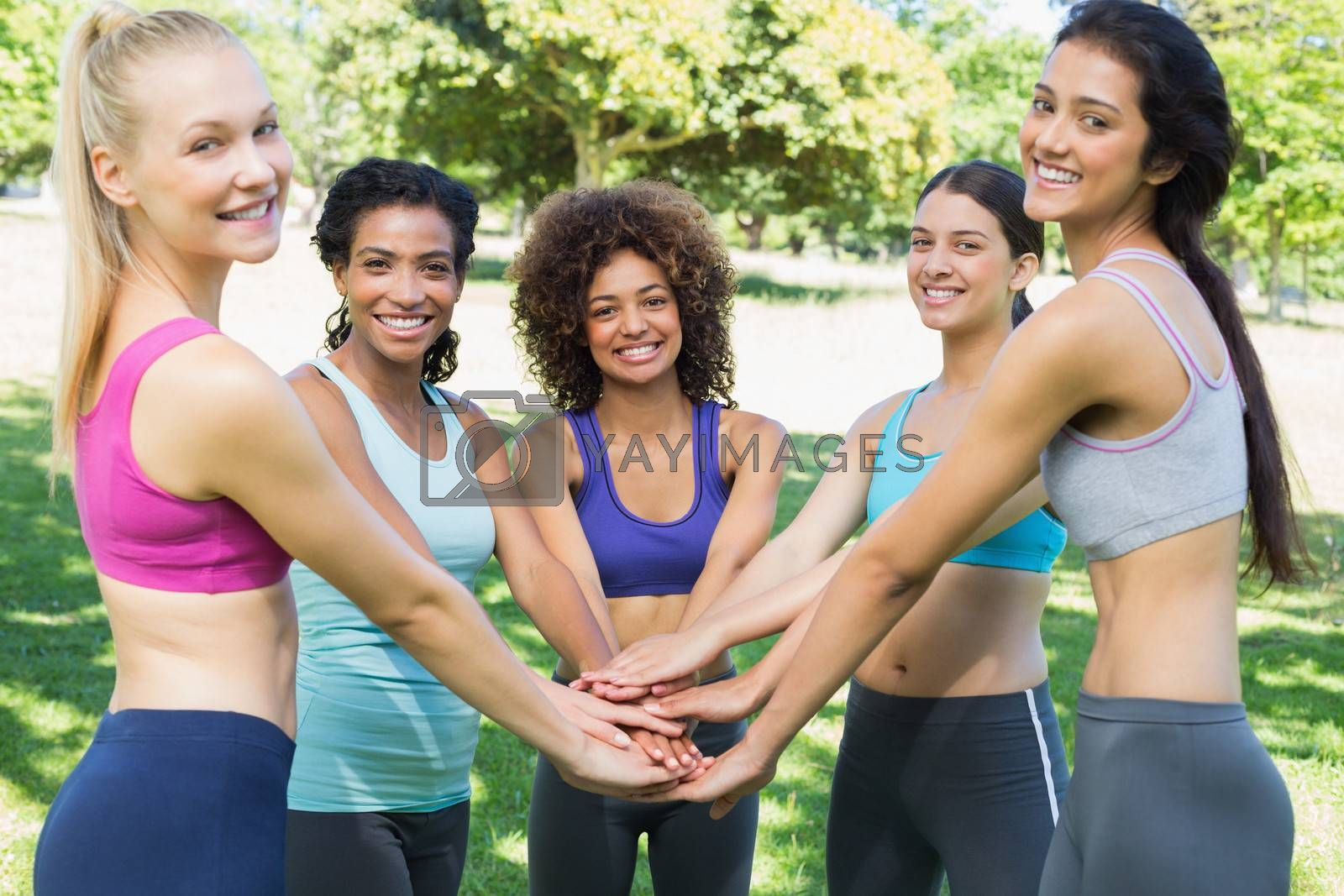 Portrait of young female friends stacking hands in the park