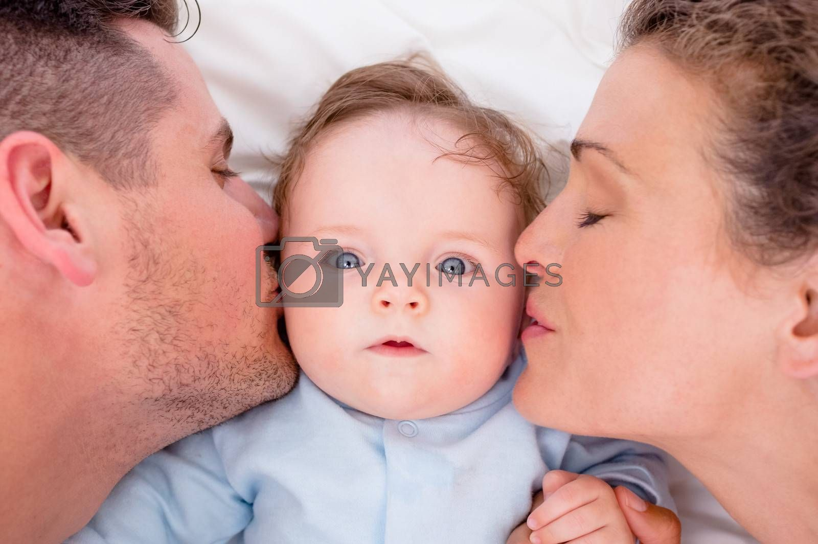 High angle of loving parents kissing baby boy in bed
