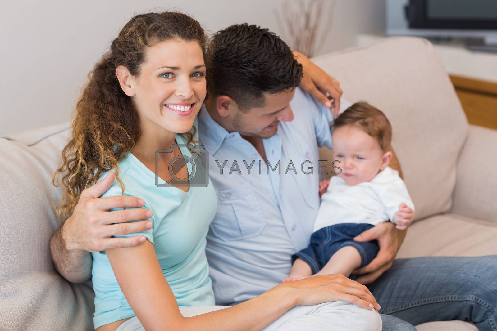 Portrait of happy woman with man holding baby in living room