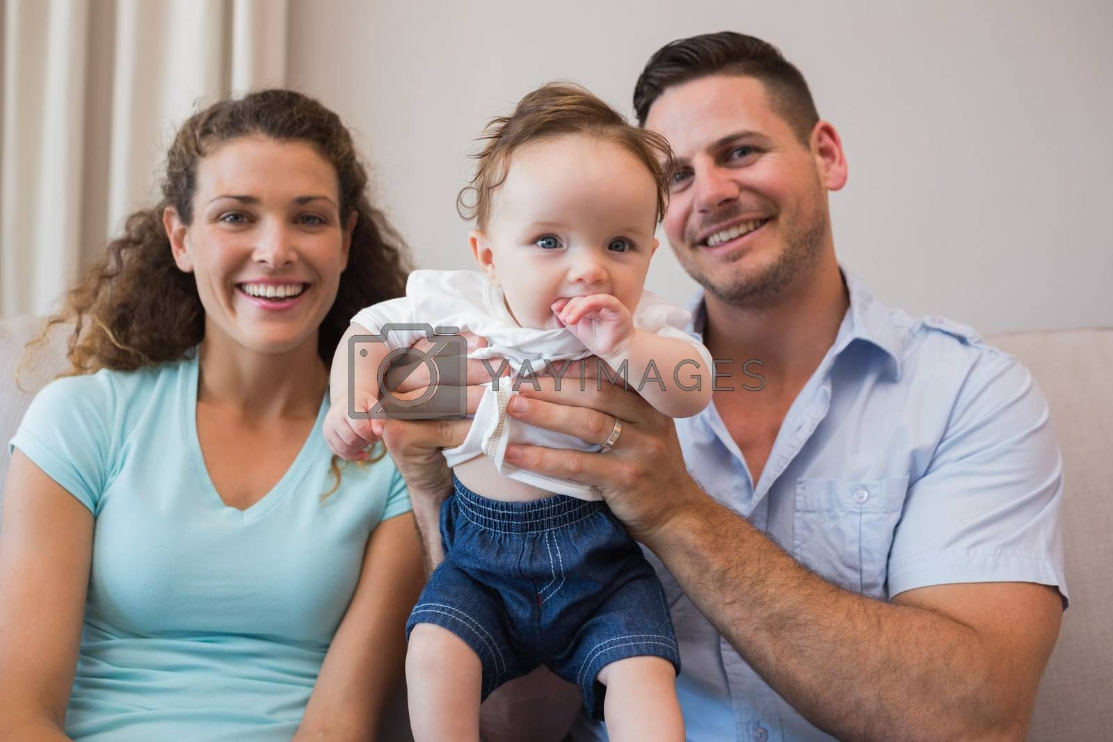 Portrait of happy parents with cute baby boy in living room