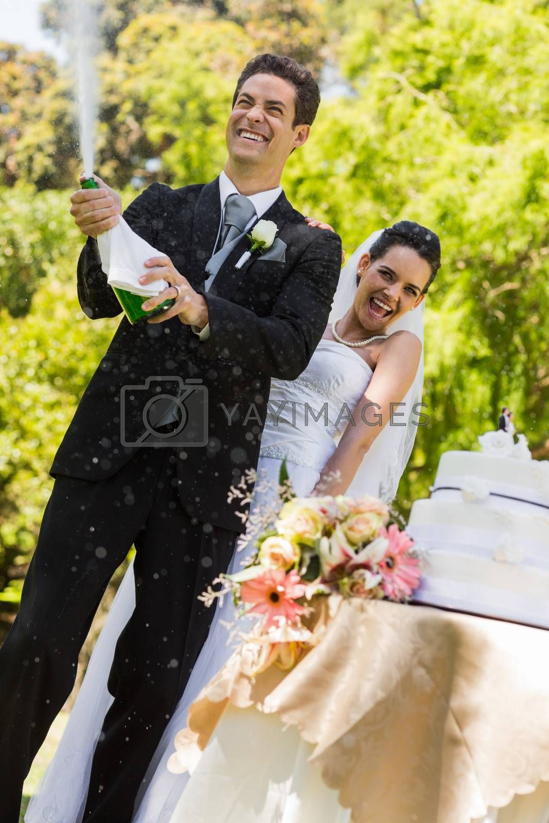 Happy young newlywed couple with groom opening the champagne bottle at park
