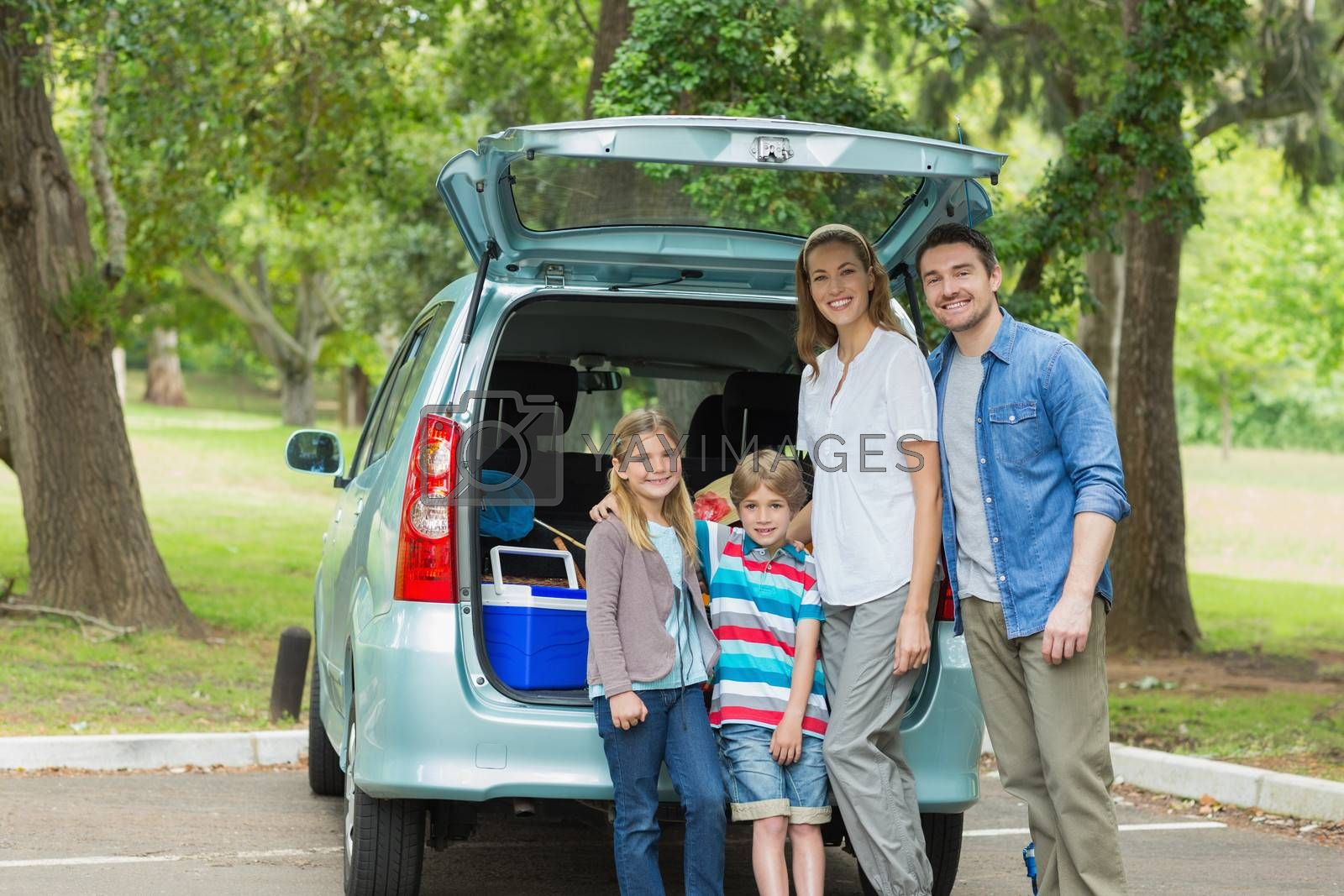 Family of four by car trunk while on picnic by Wavebreakmedia