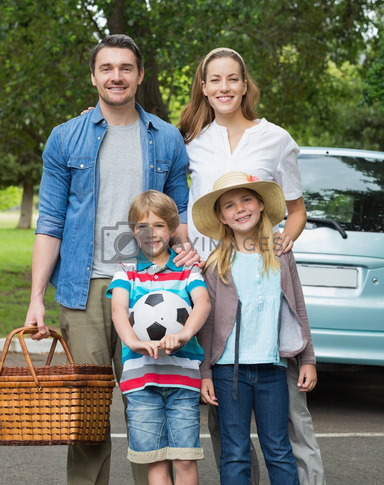 Happy family of four with picnic basket by Wavebreakmedia