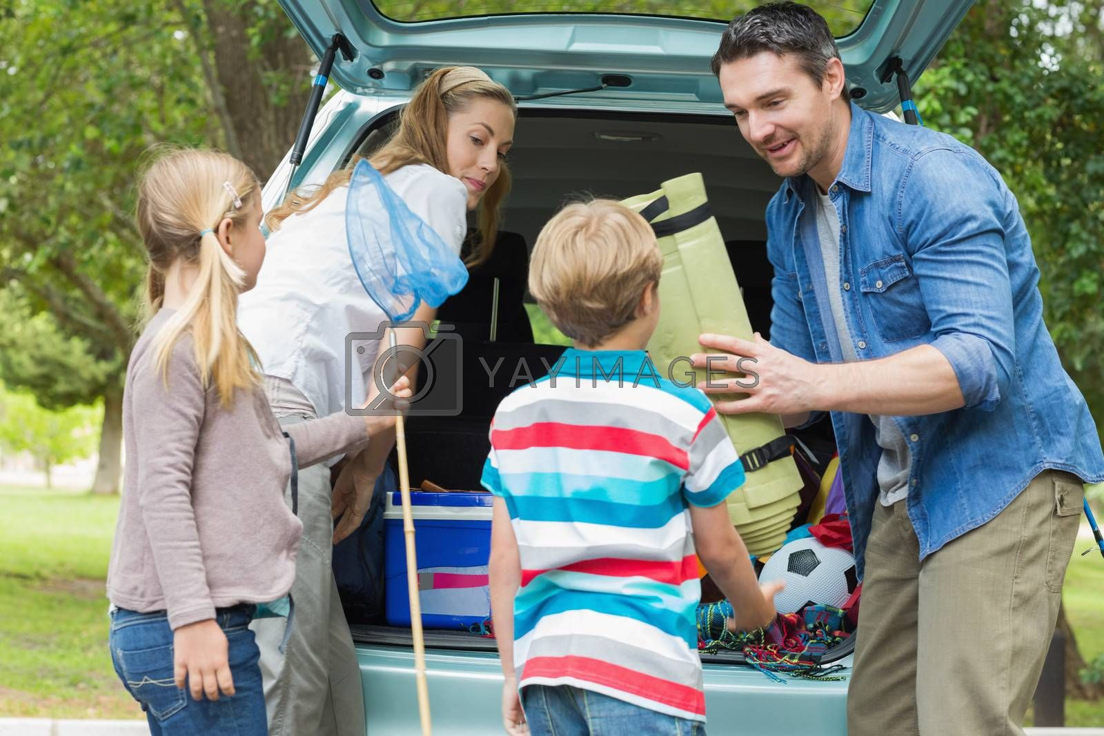 Happy family of four unloading car trunk while on picnic