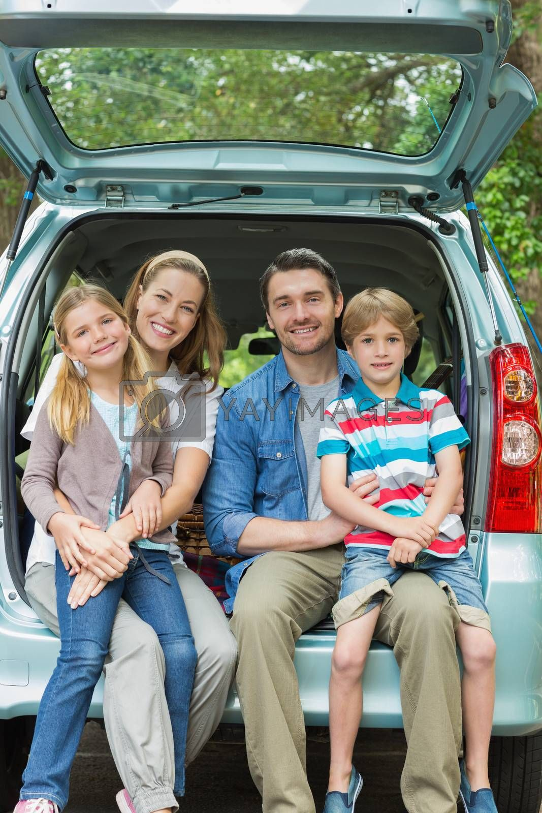 Happy family of four sitting in car trunk by Wavebreakmedia