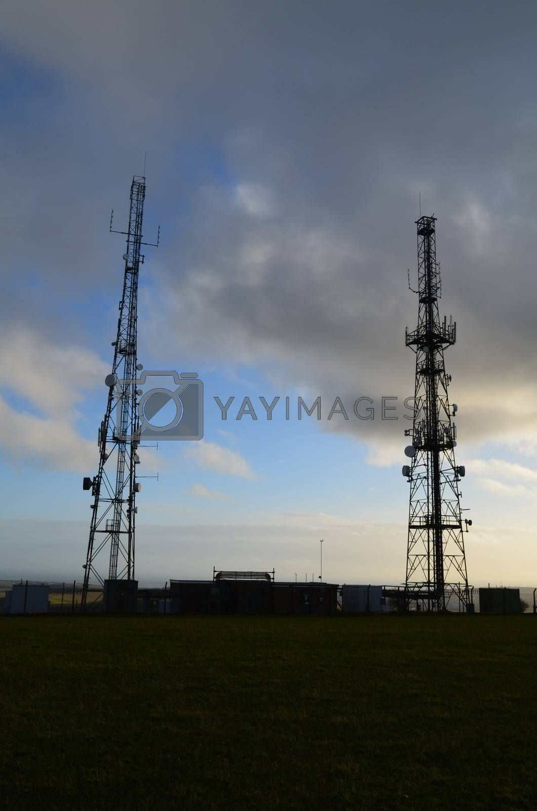 Two large communication masts on the Sussex hill of Firle Beacon.