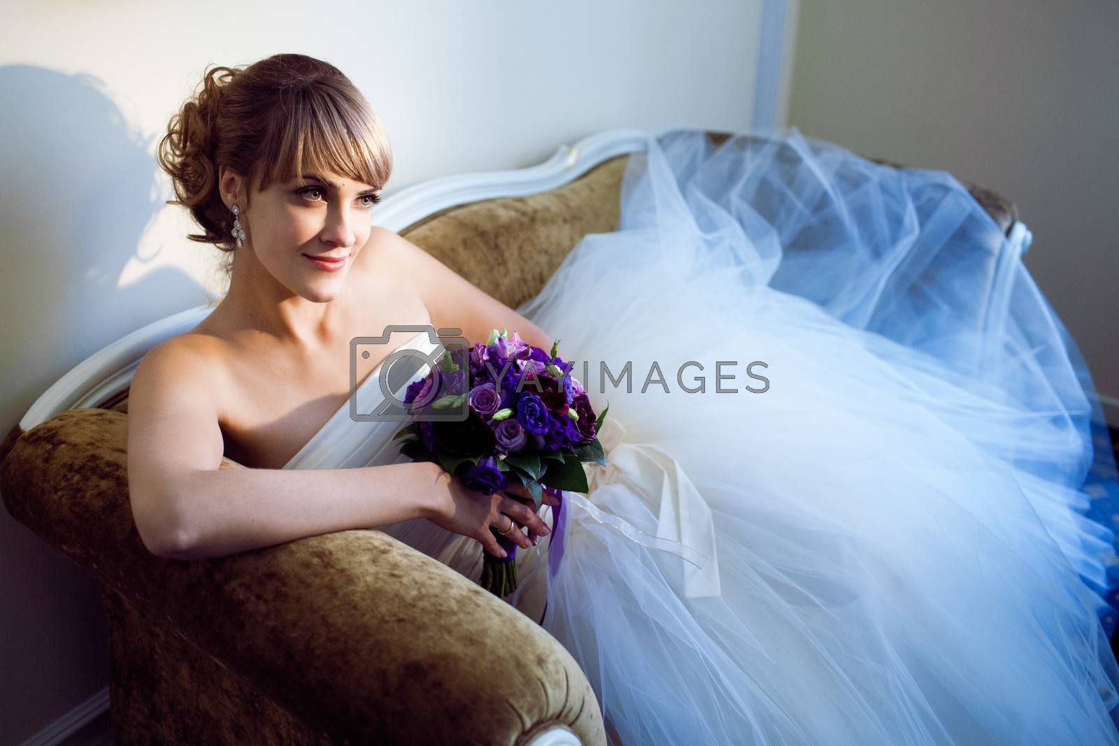 young bride with flowers on the sofa