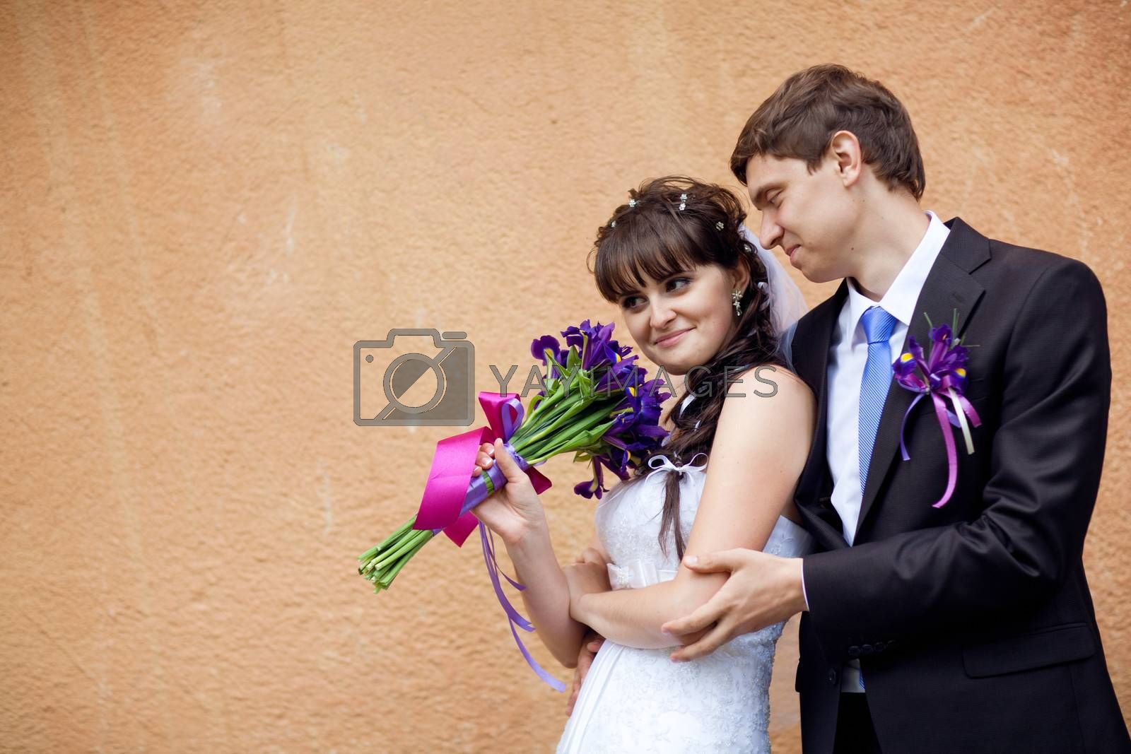bride and groom by the wall