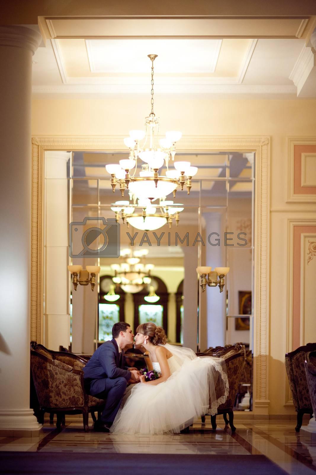 bride and groom in golden hall