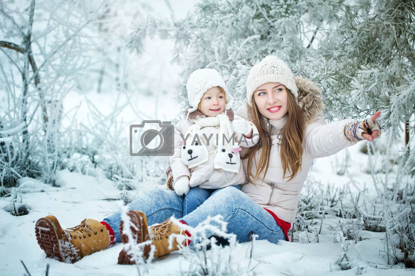 Attractive young mother holds daughter on hands and shows the side