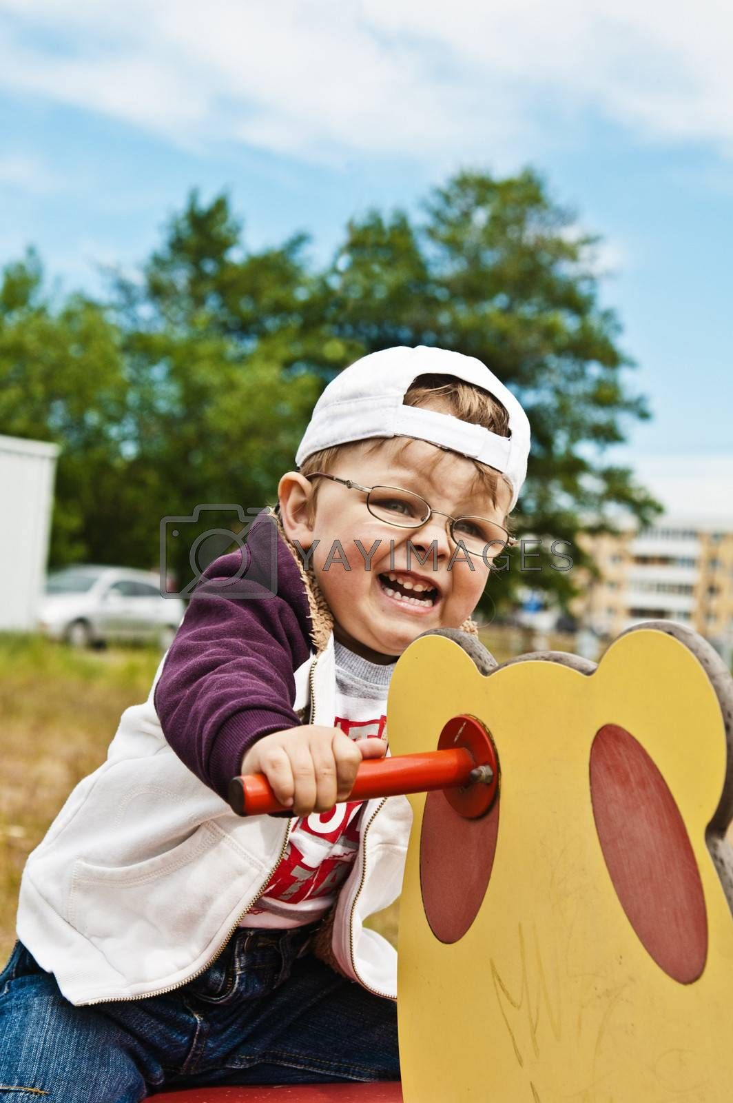 Little boy is himself a biker, swinging on a swing