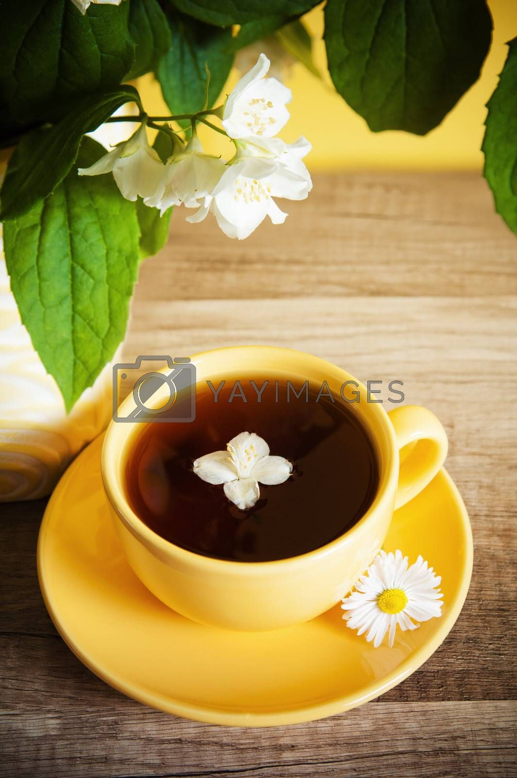 Cup of tea and a bouquet of blooming Jasmine