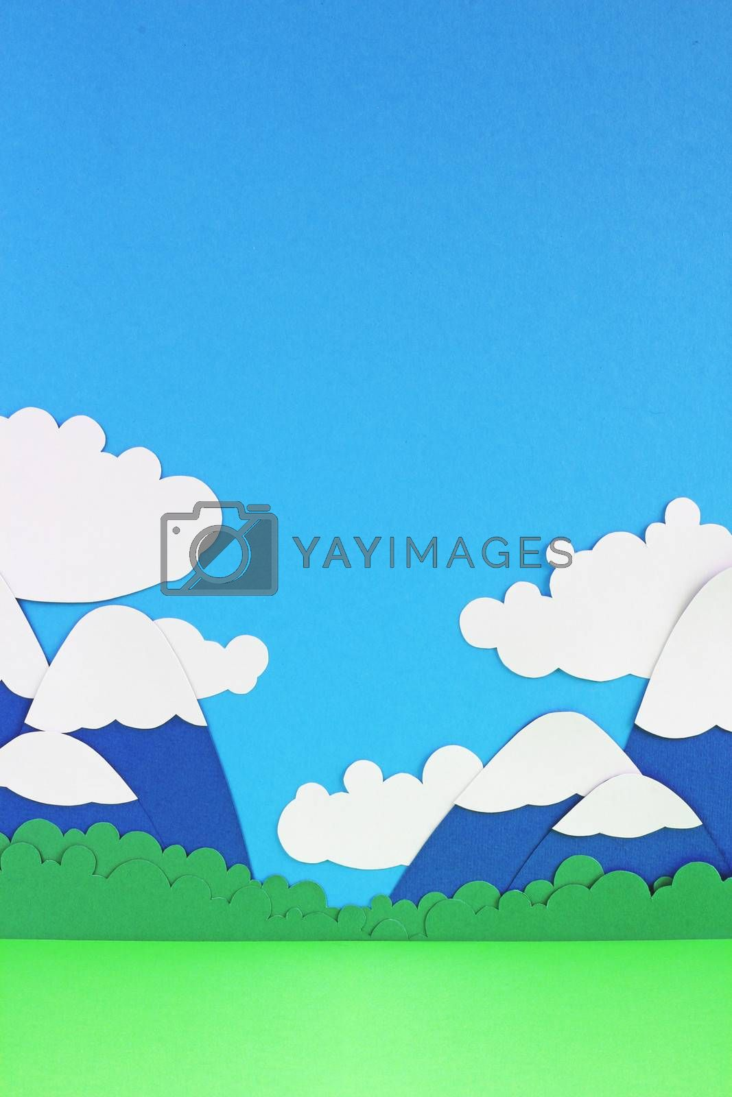 Paper landscape with mountains, trees, clouds and meadow