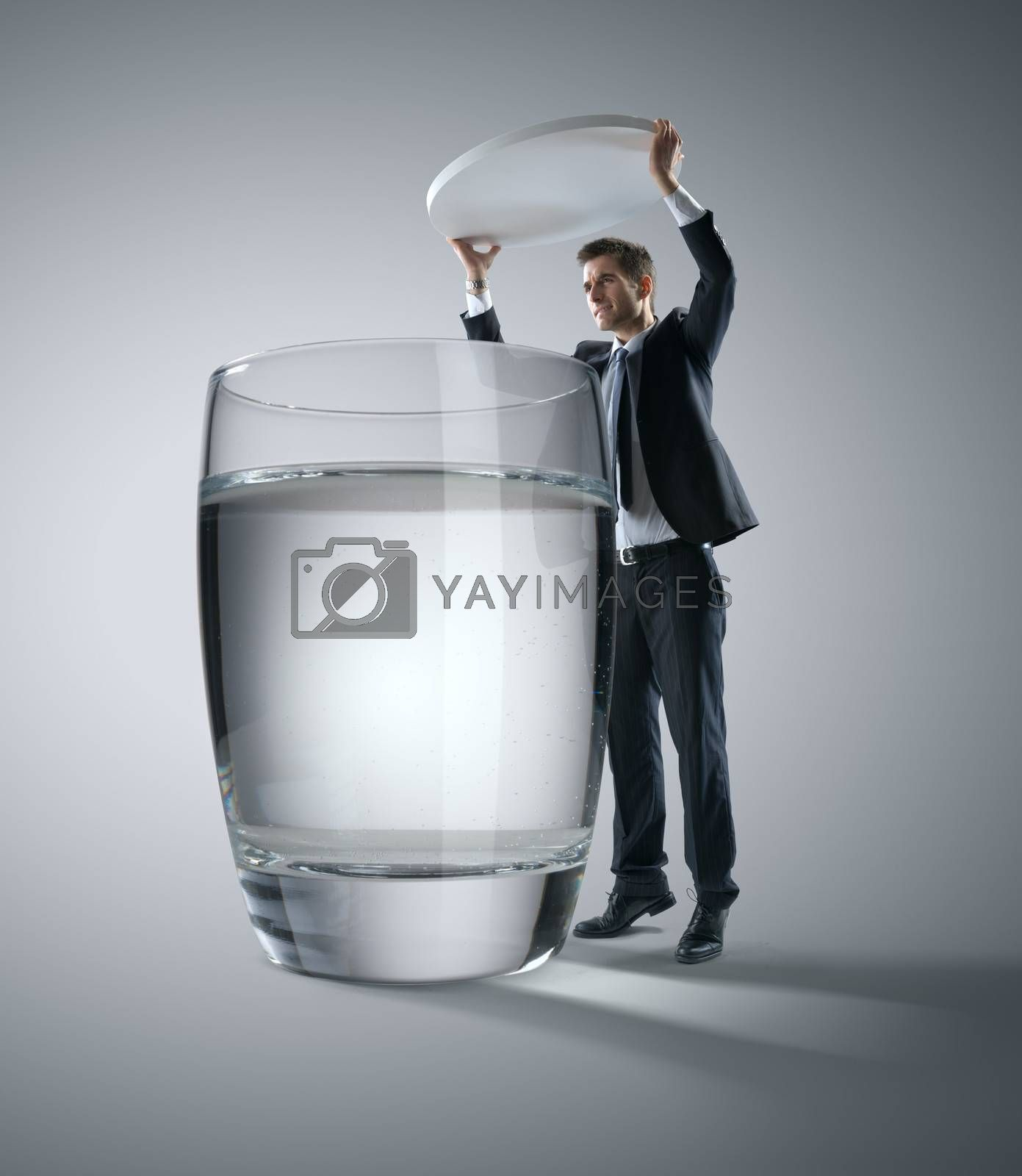 Businessman putting a huge pill into a glass of water.