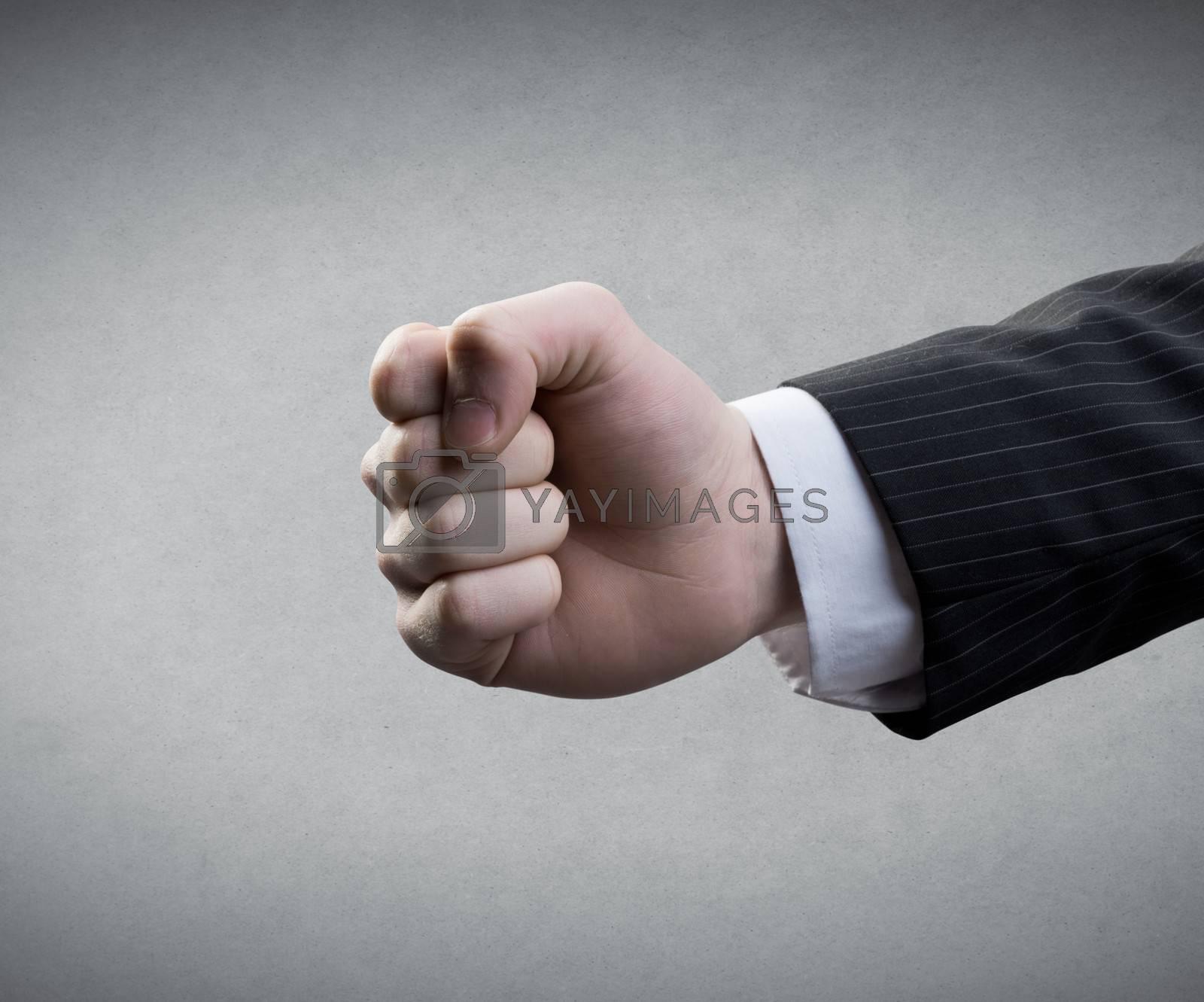 Businessman's fist on gray background