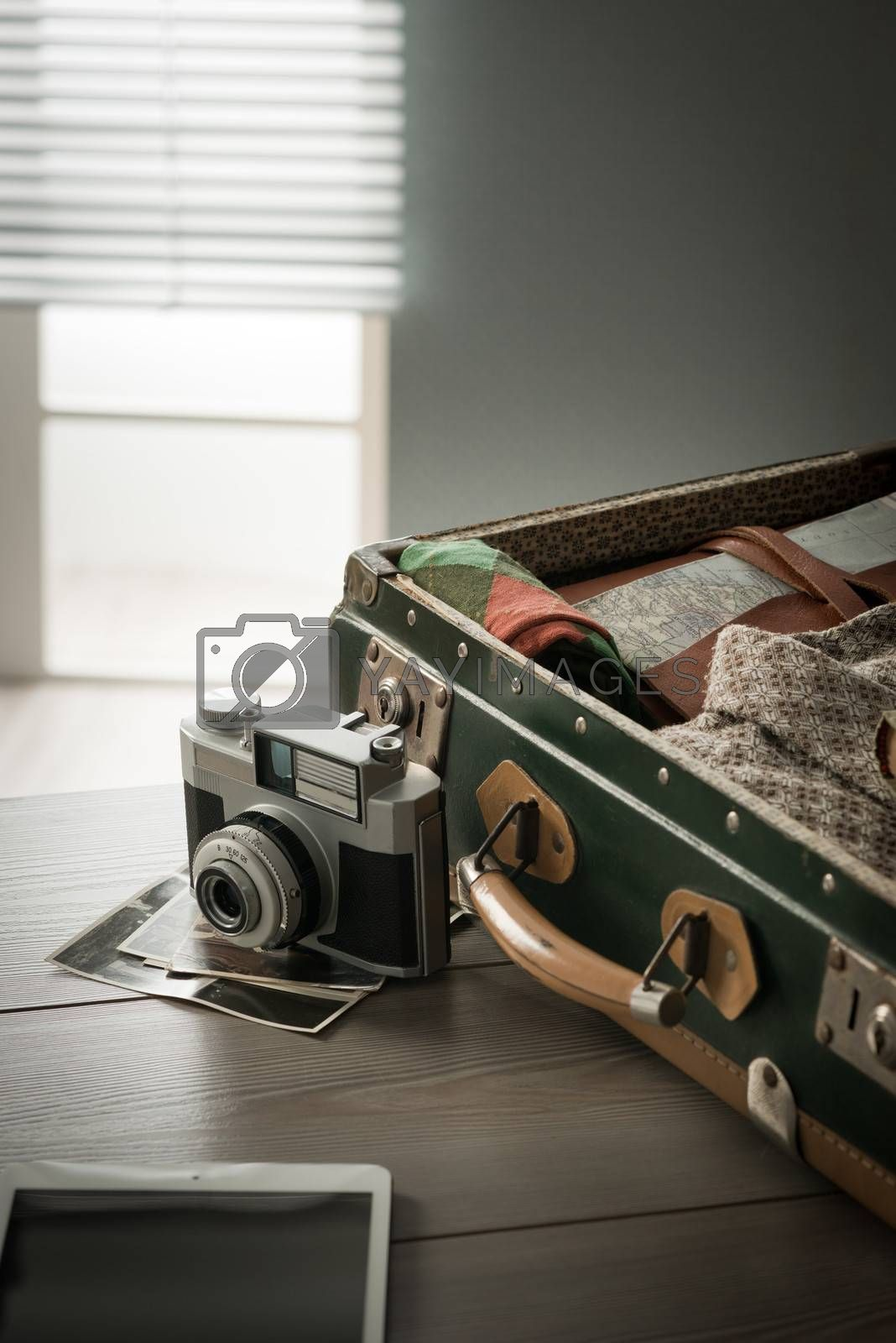 Traveler's suitcase with vintage equipment with camera and old pictures.