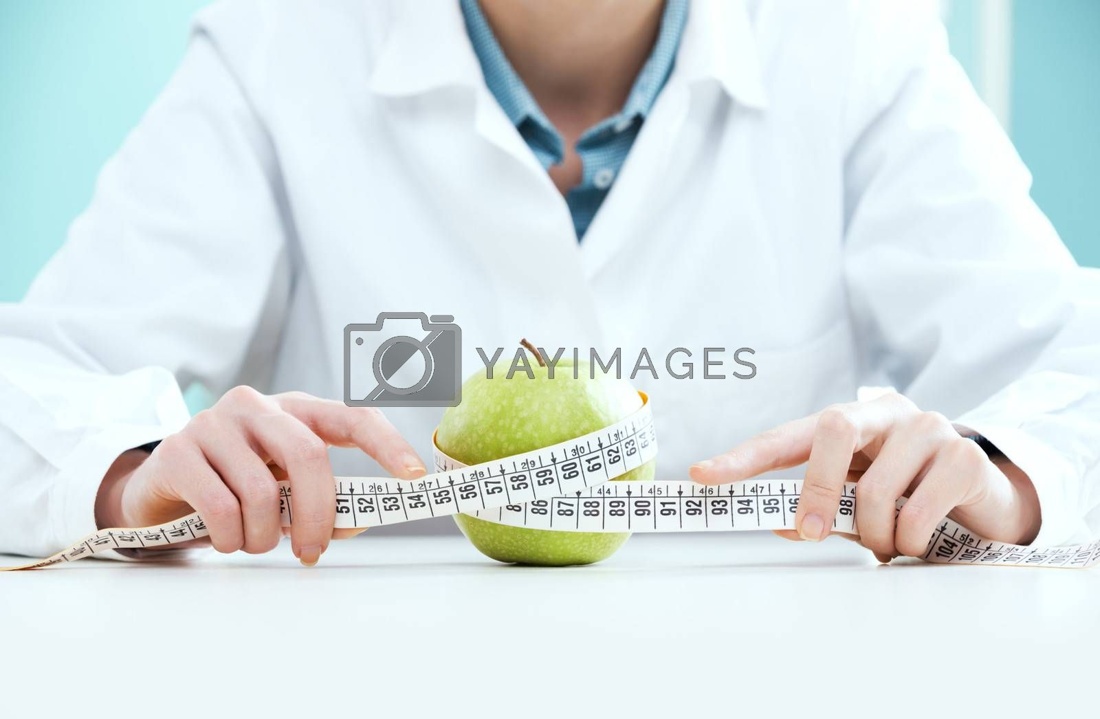 Young female doctor holding measuring tape and apple