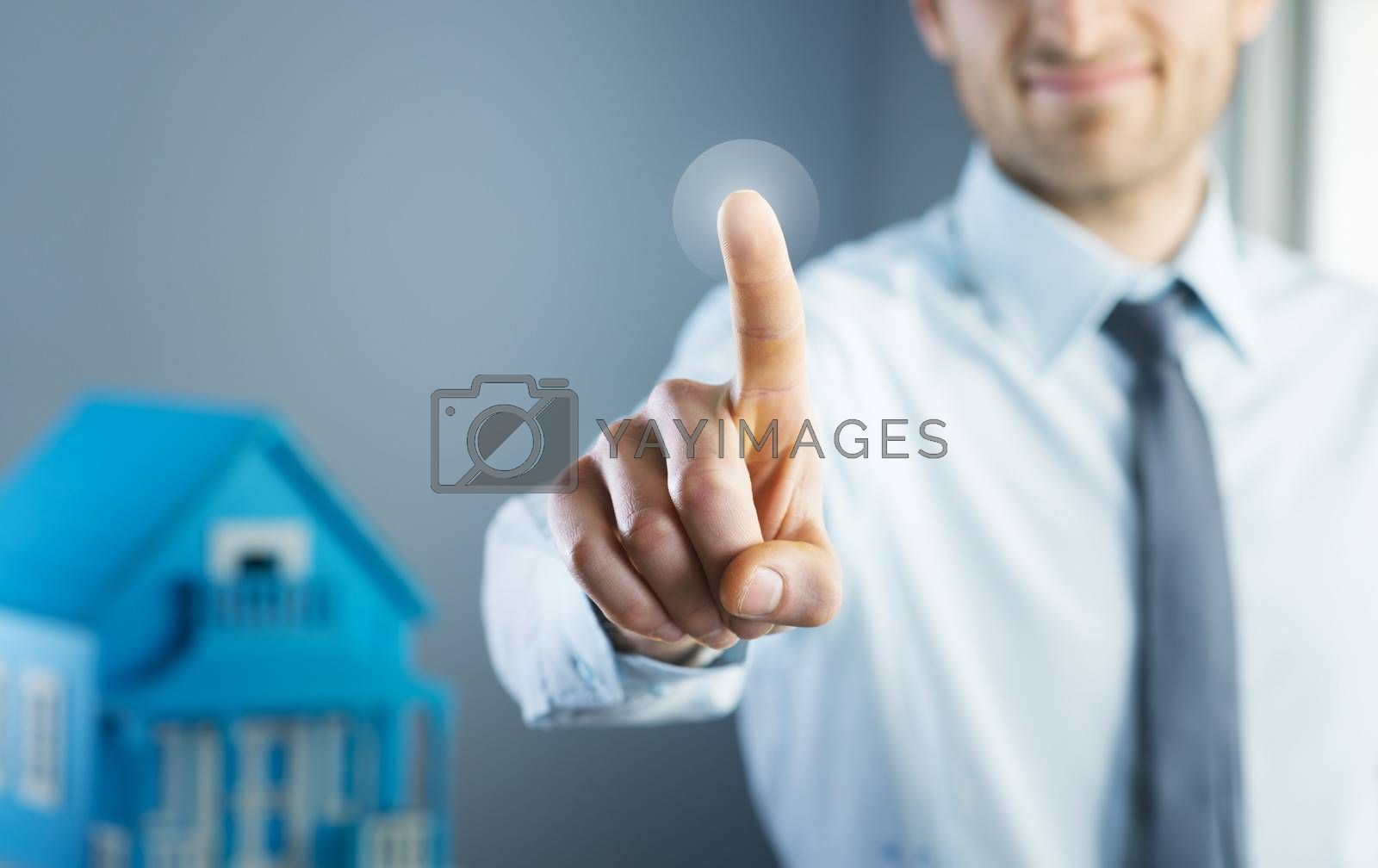 Man using touch screen interface with model house on background.