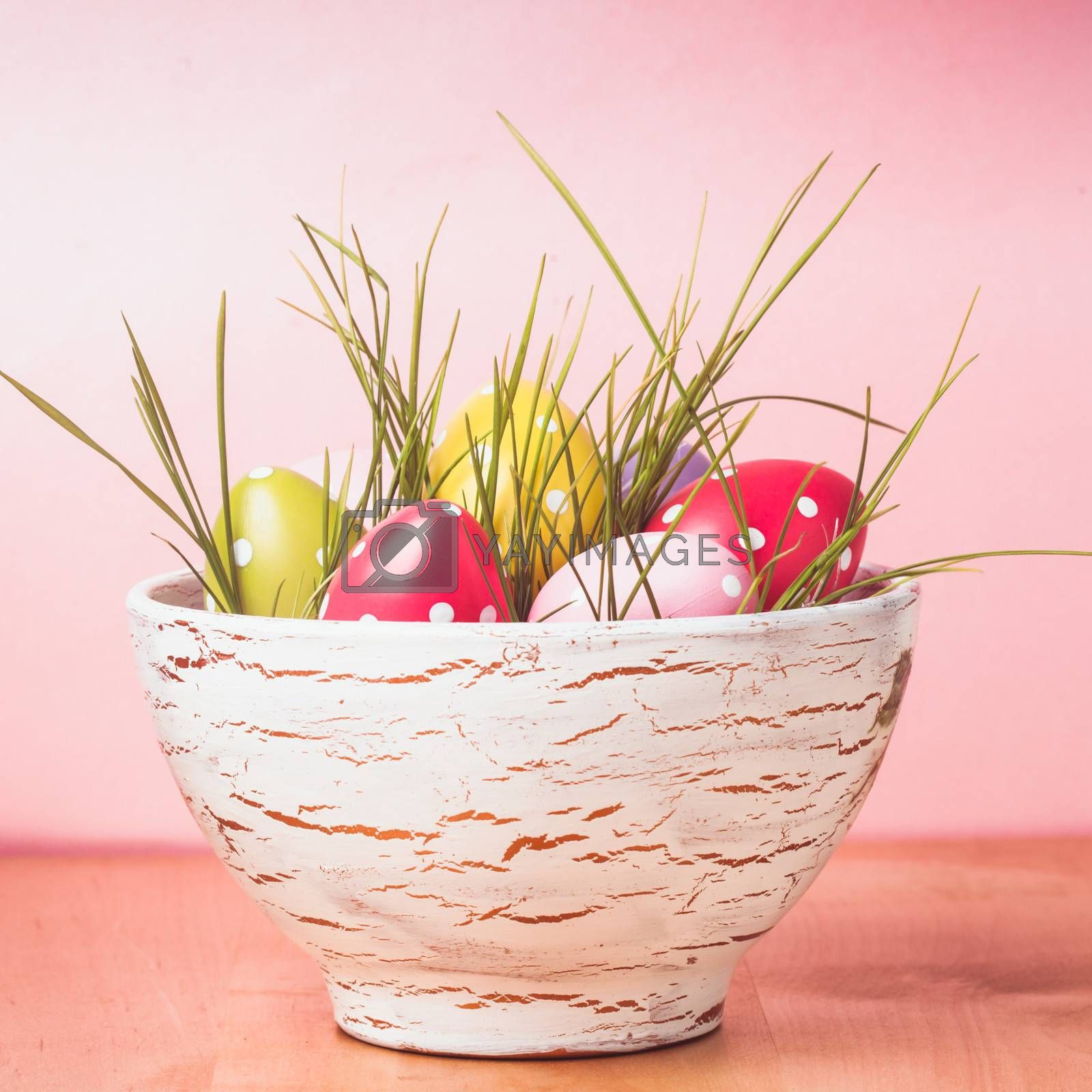 Decorative eggs in pot with grass over pink background. Easter decor.