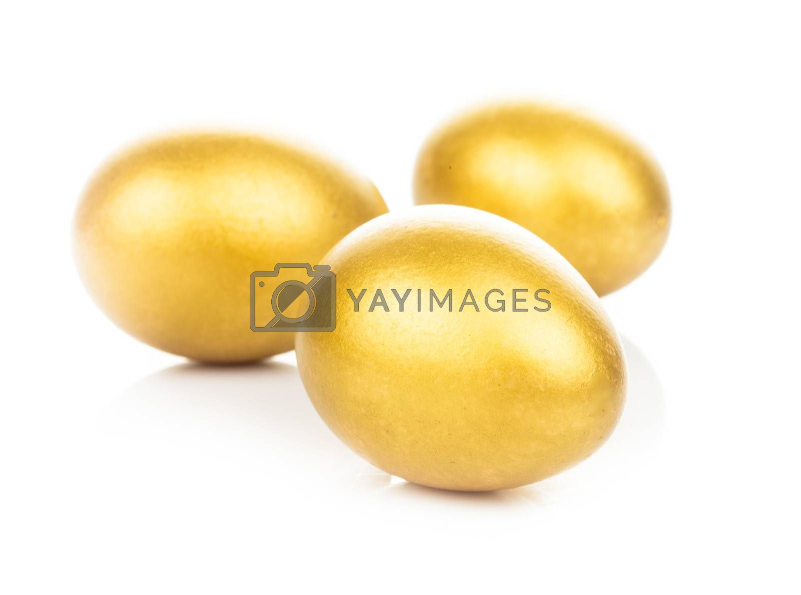 Three golden eggs isolated on white background