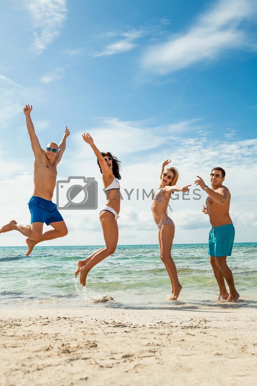 young happy friends havin fun on the beach by juniart