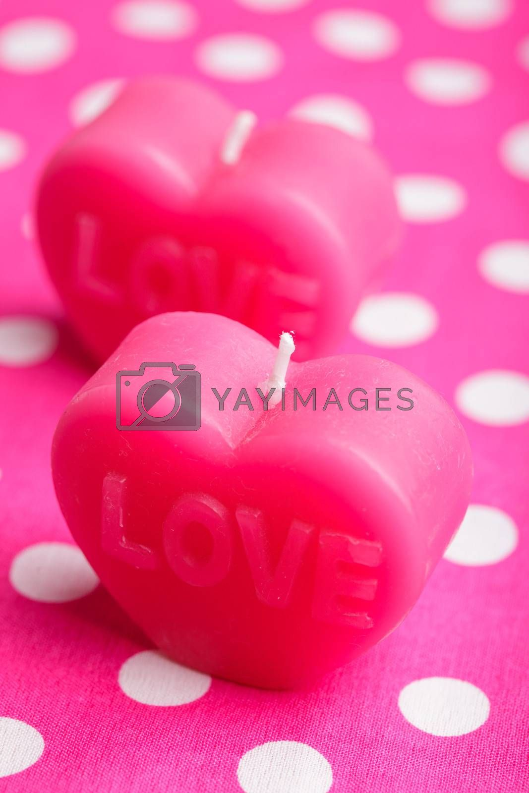 Red scented candle in the shape of heart closeup on the pink background