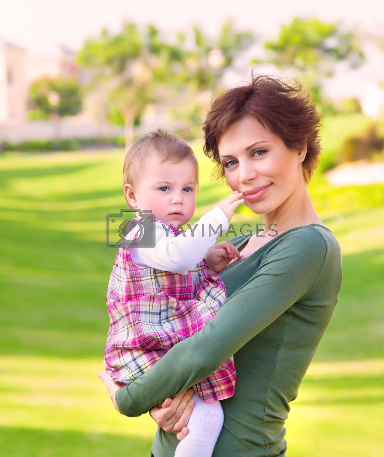 Mother with baby daughter having fun outdoor, relaxation on backyard, walking in the park, enjoying warm spring weather