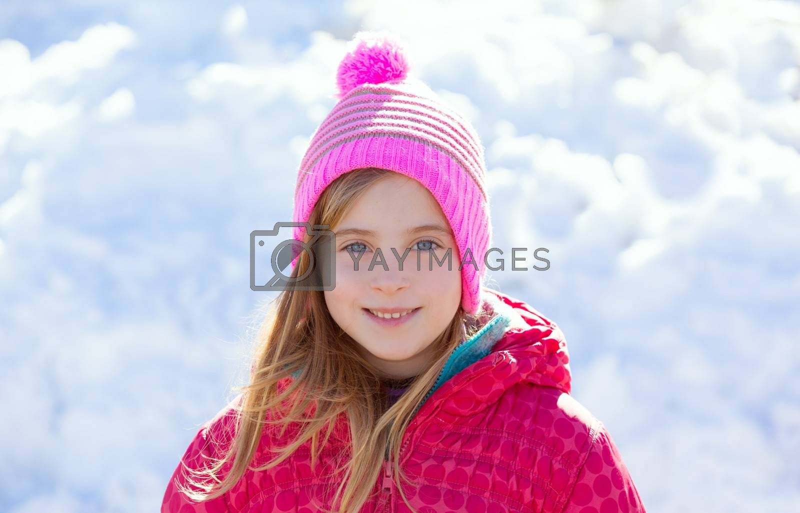 Blond kid girl winter pink hat in the snow smiling happy