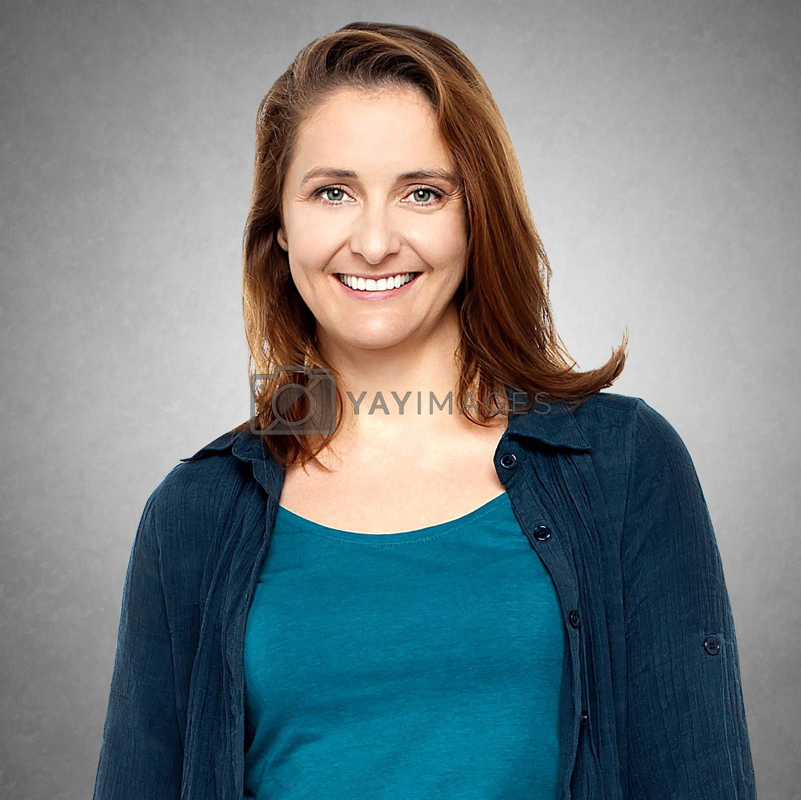 Smiling middle aged woman isolated against grey background