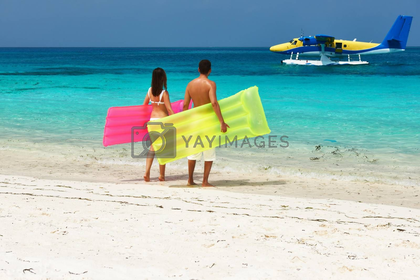 Couple with inflatable rafts looking at arrived seaplane on a tropical beach at Maldives. No brand names or copyright objects