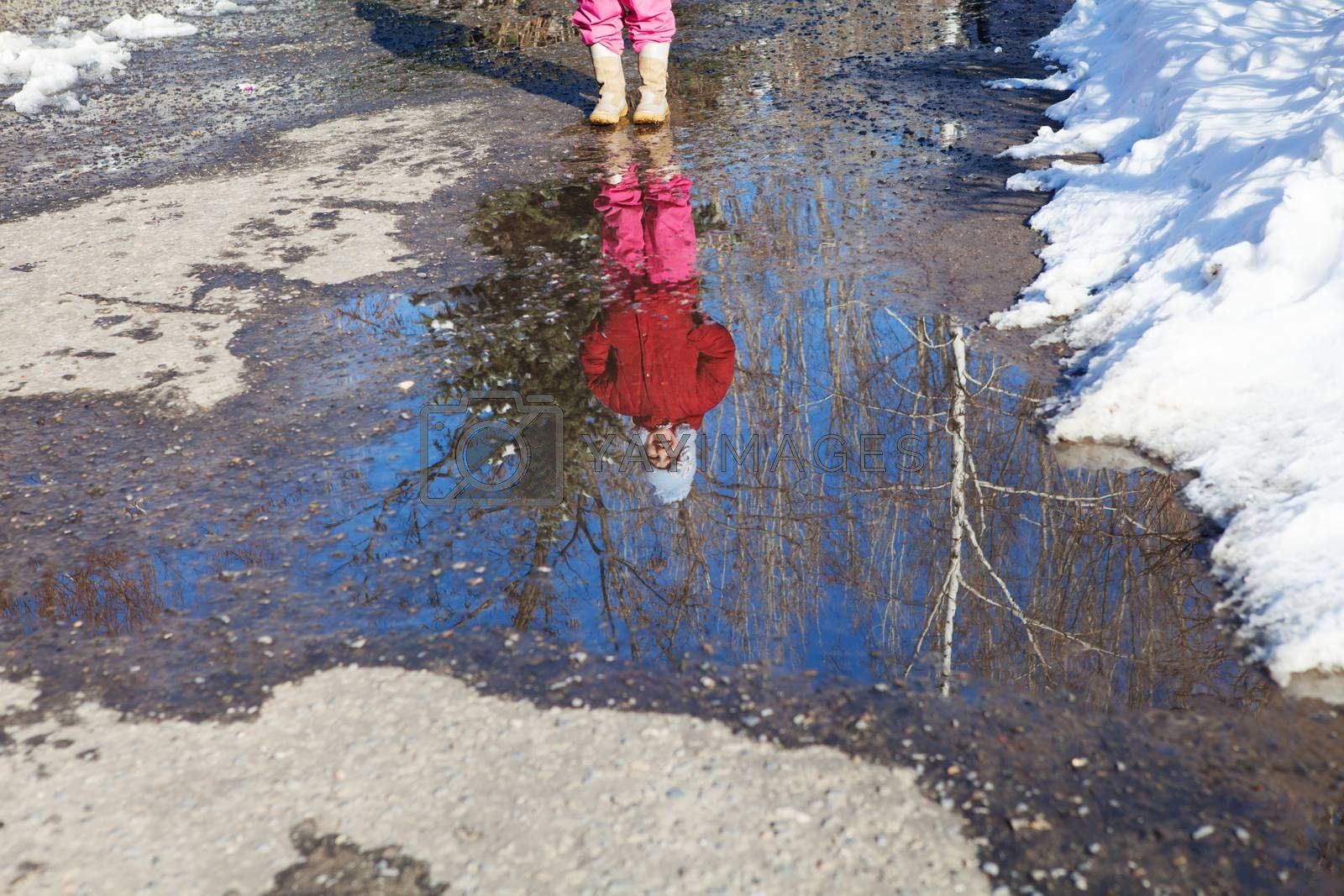 reflection of small girl in spring puddle