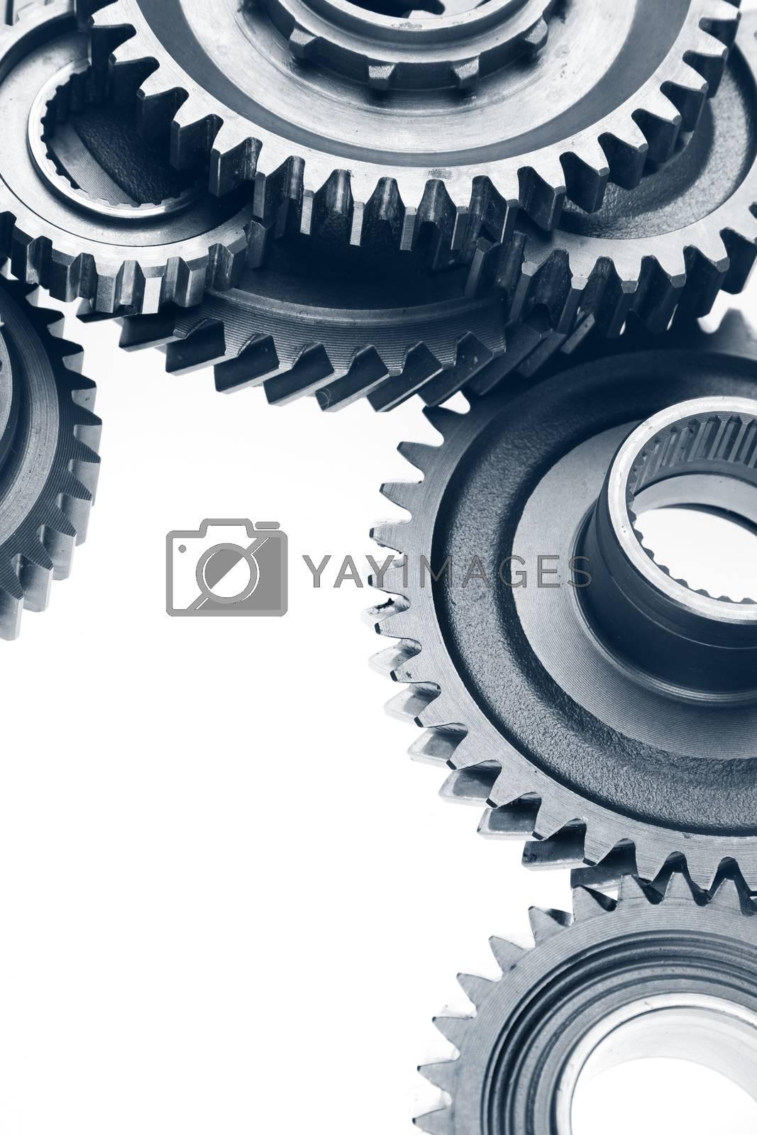 Metal cog gears bonding together on plain background