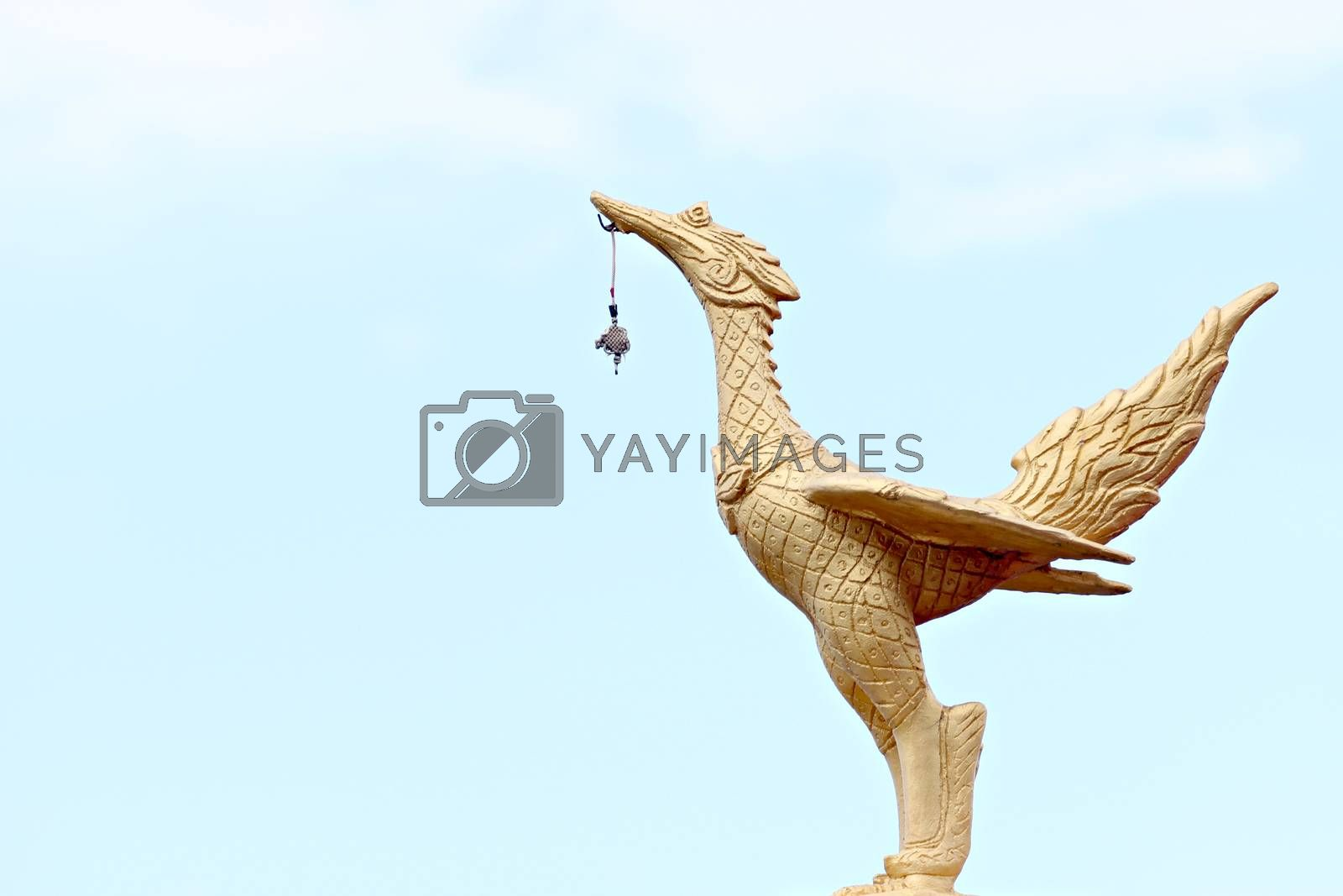 Golden swan statue on blue sky.