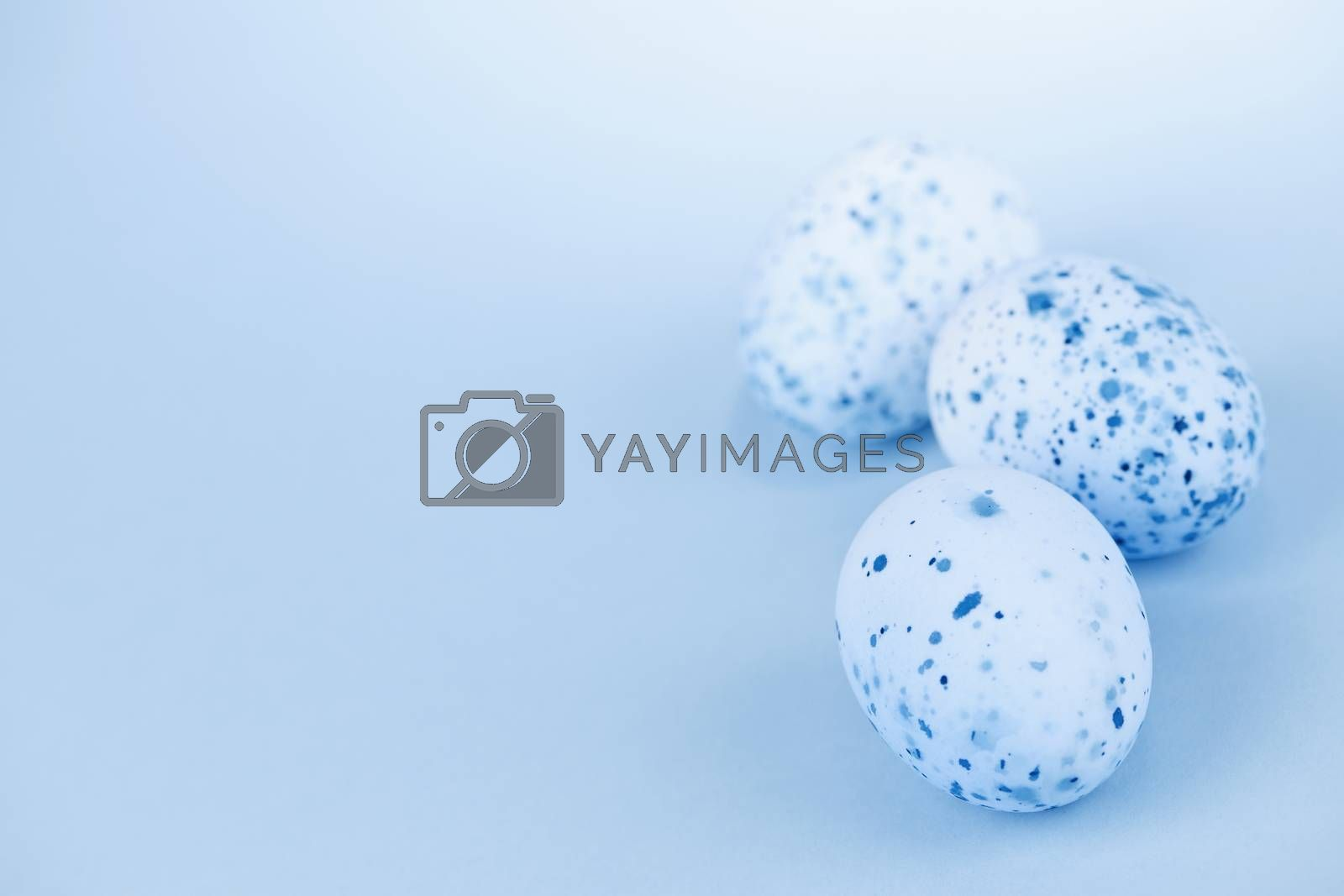 Three pale blue speckled painted easter eggs with copy space