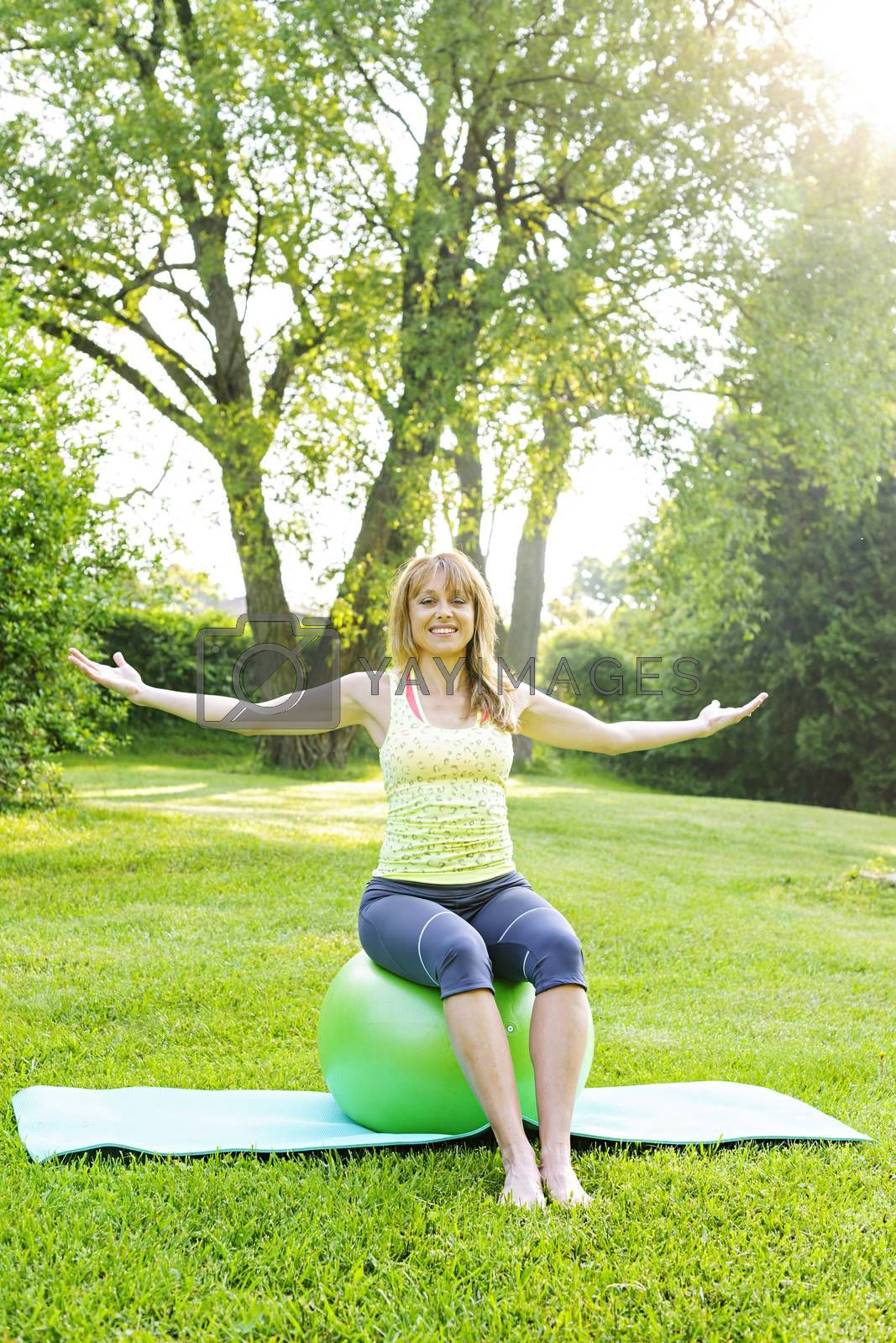 Female fitness instructor sitting on yoga exercise ball in green park