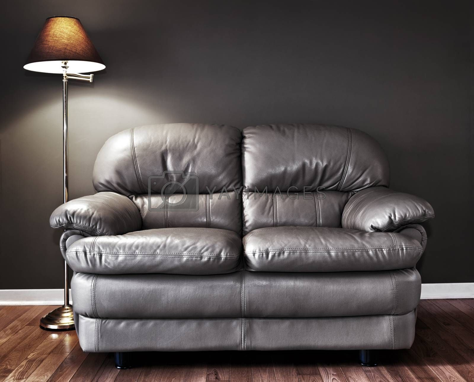 Leather love seat and floor lamp against dark wall