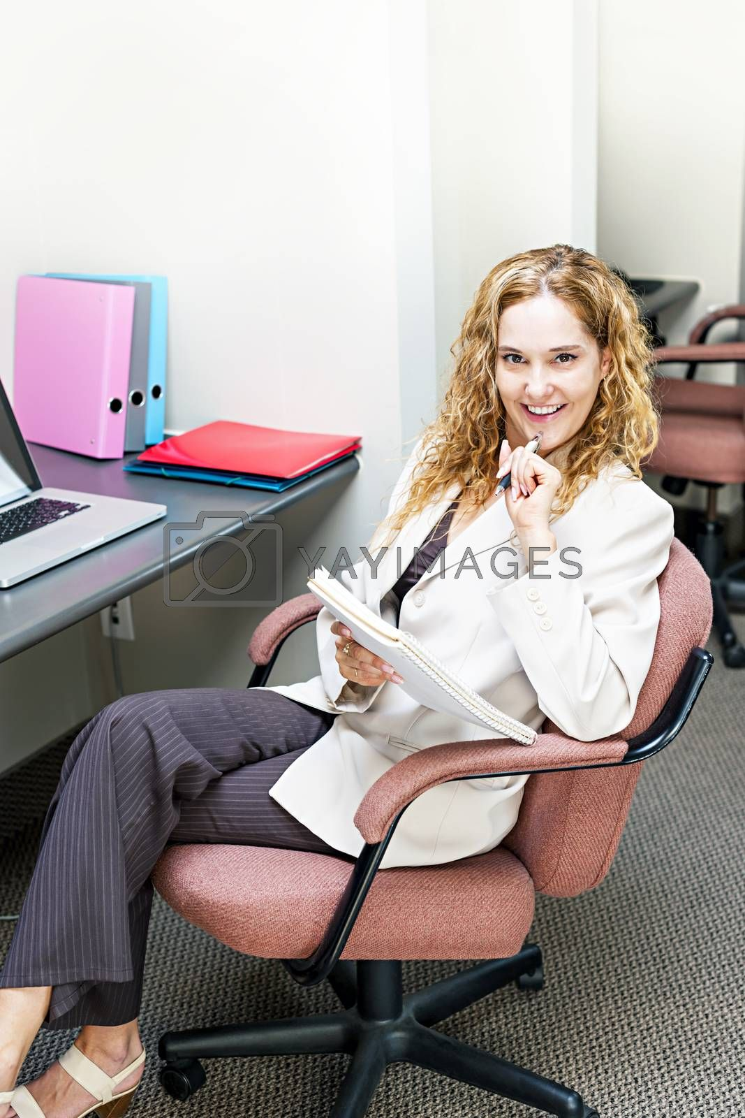 Smiling businesswoman thinking of ideas in office workstation