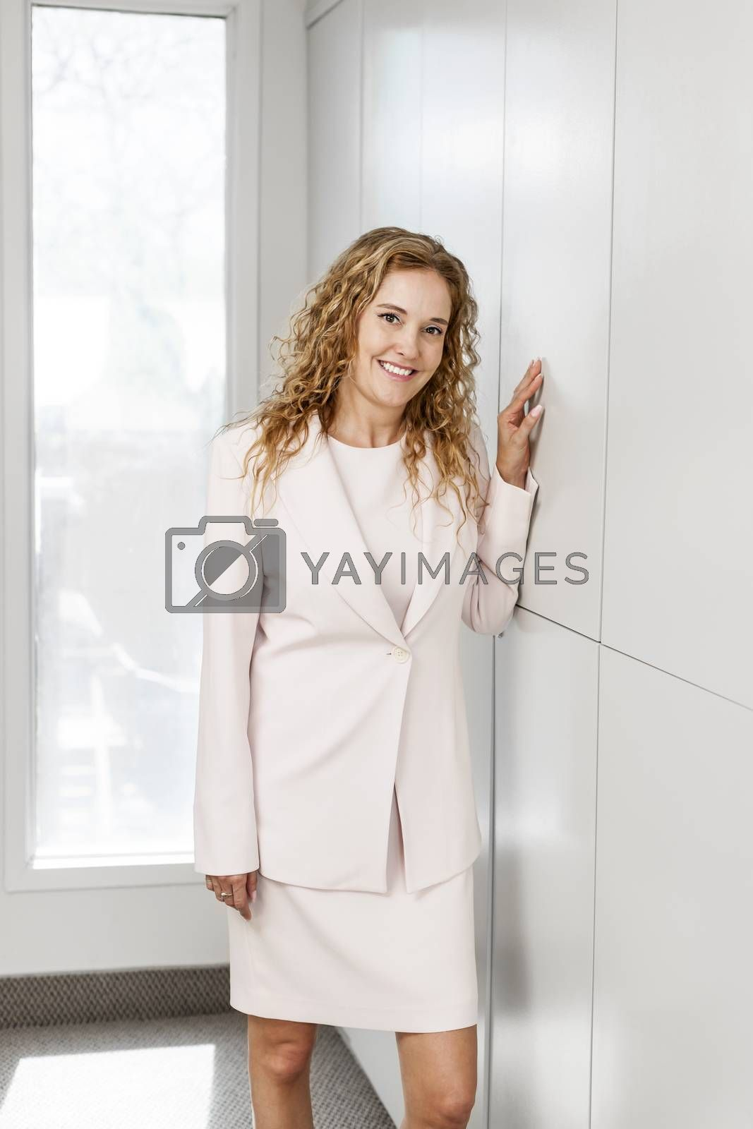 Smiling business woman standing in office hallway