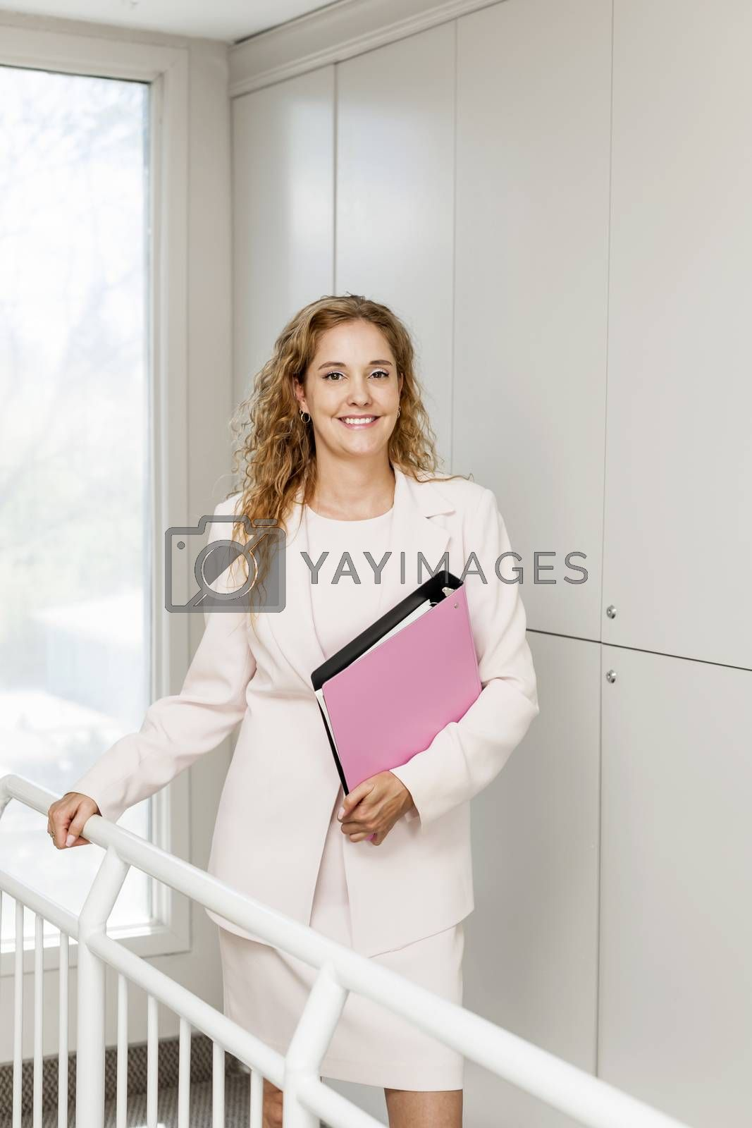 Smiling powerful business woman standing in office hallway holding binder