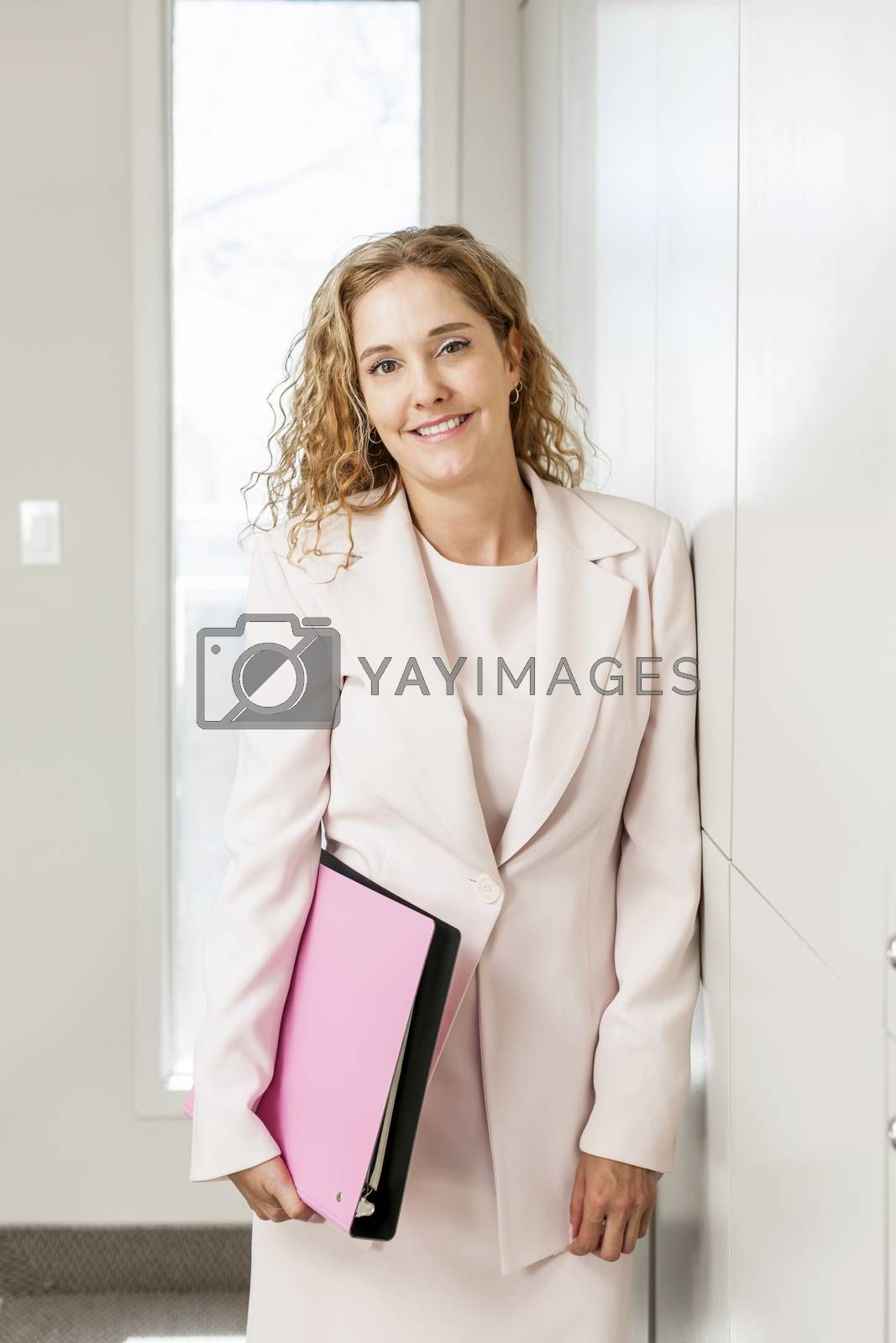 Smiling successful business woman standing in office hallway holding binder