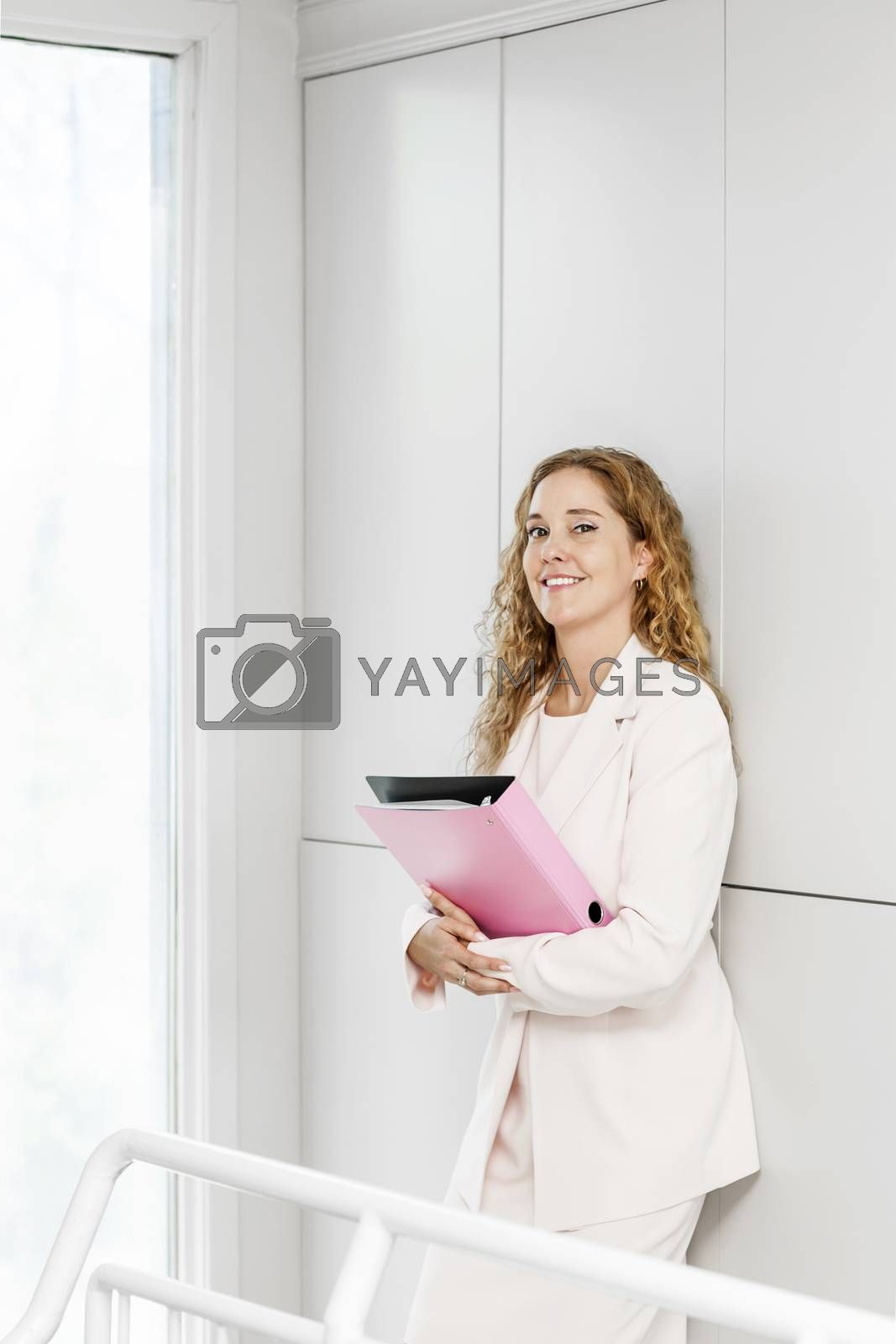 Confident career business woman standing in office hallway holding binder