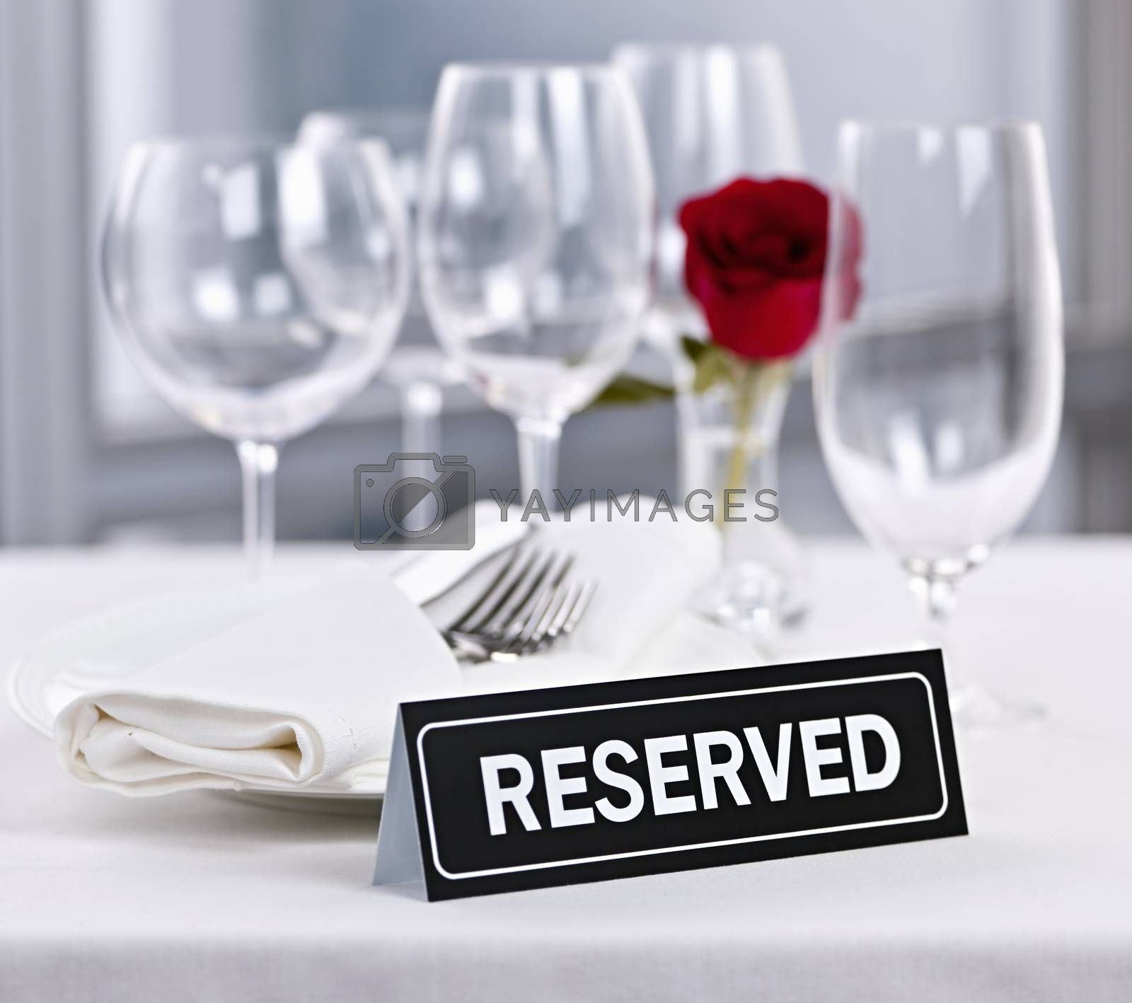 Reserved romantic restaurant table setting with roses plates and cutlery
